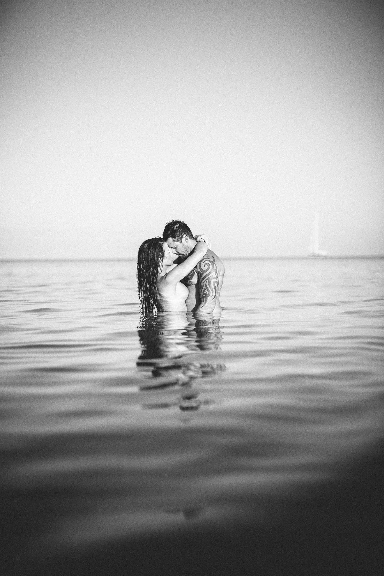 Bride and groom kissing topless in the sea