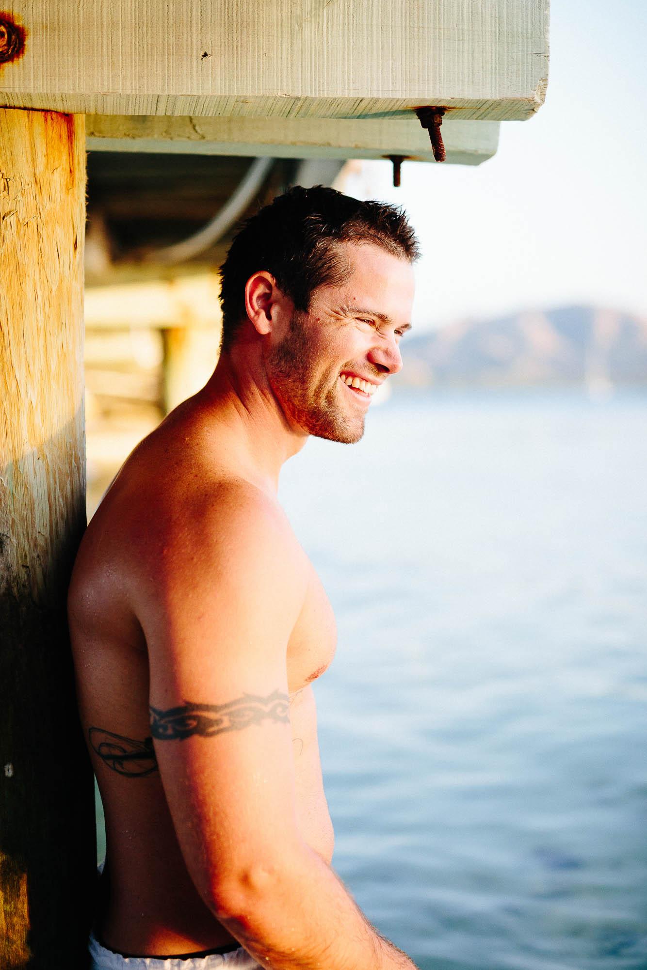 Groom shirtless under the pier