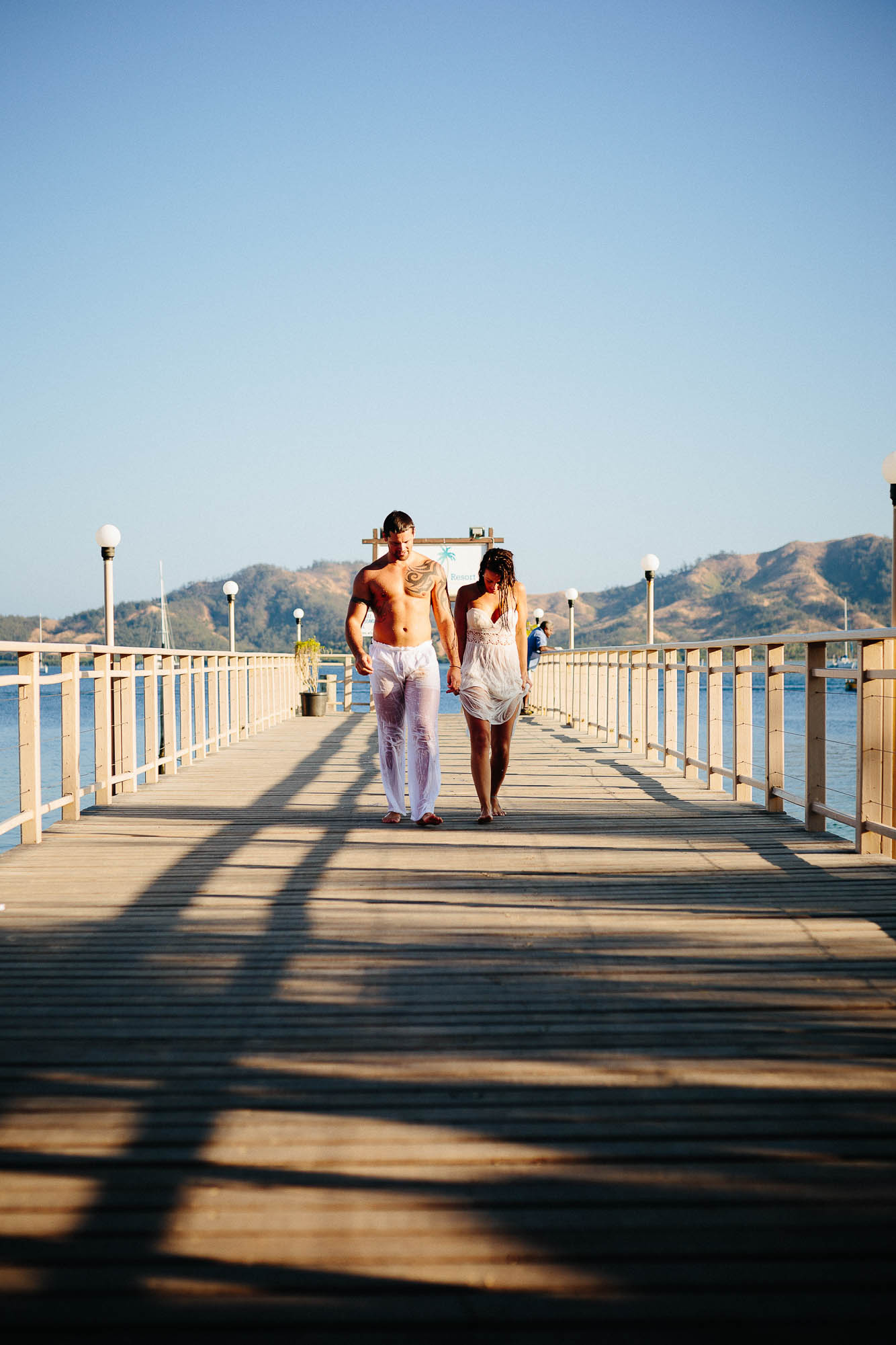 couple walking down the jetty after their trash-the-dress session