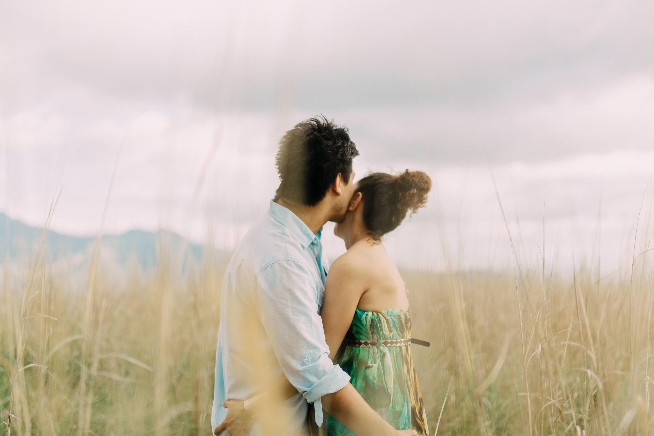 Sean kissing his bride to be on the cheek in tall grass