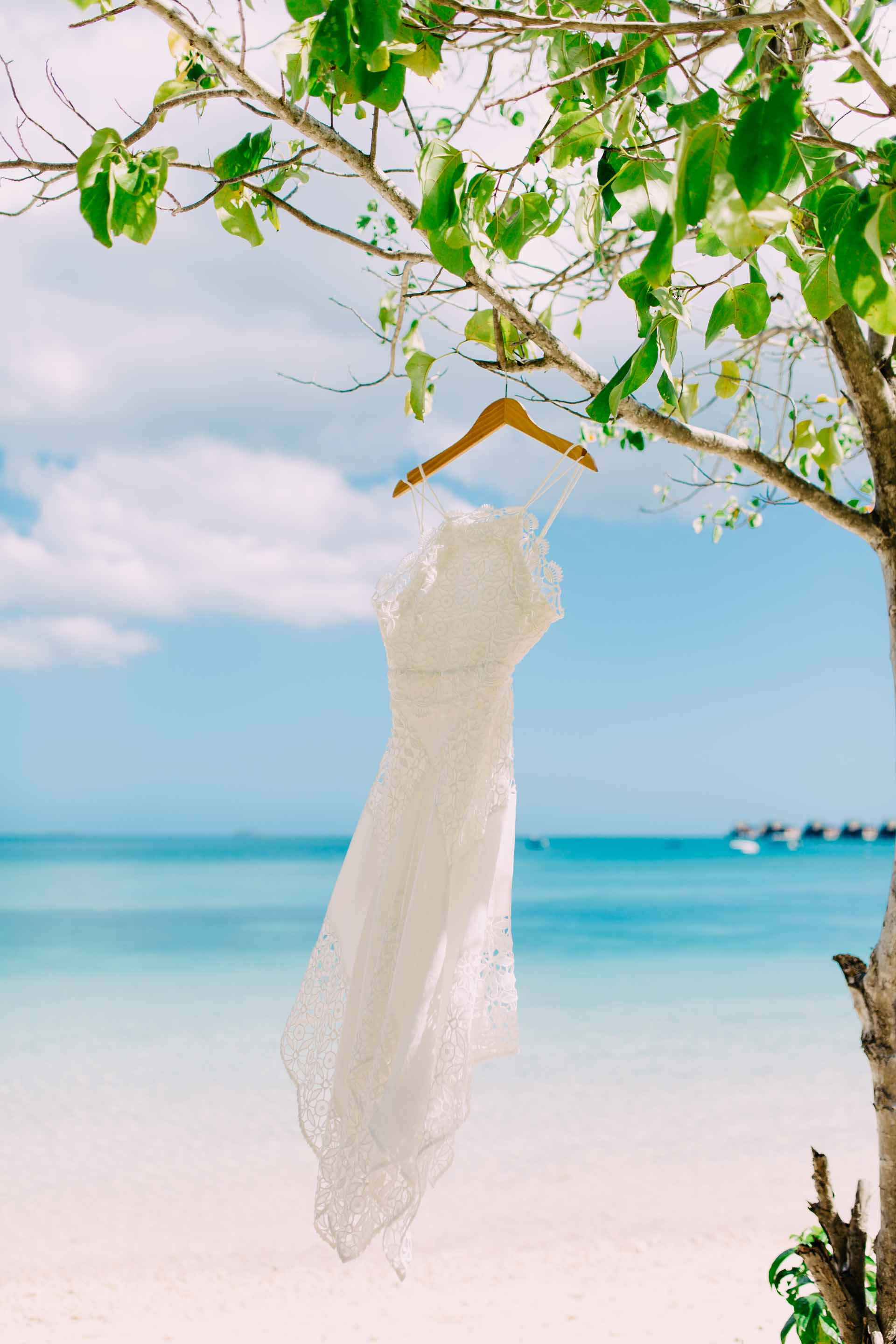 Brides dress hanging from a tree on the white sandy beach