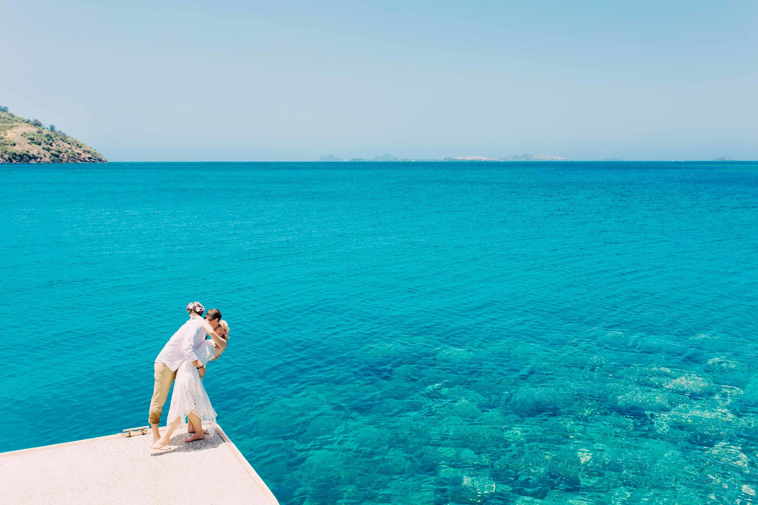 the couple dipping and kissing with the stunning blues and vibrant colours of the reef behind them