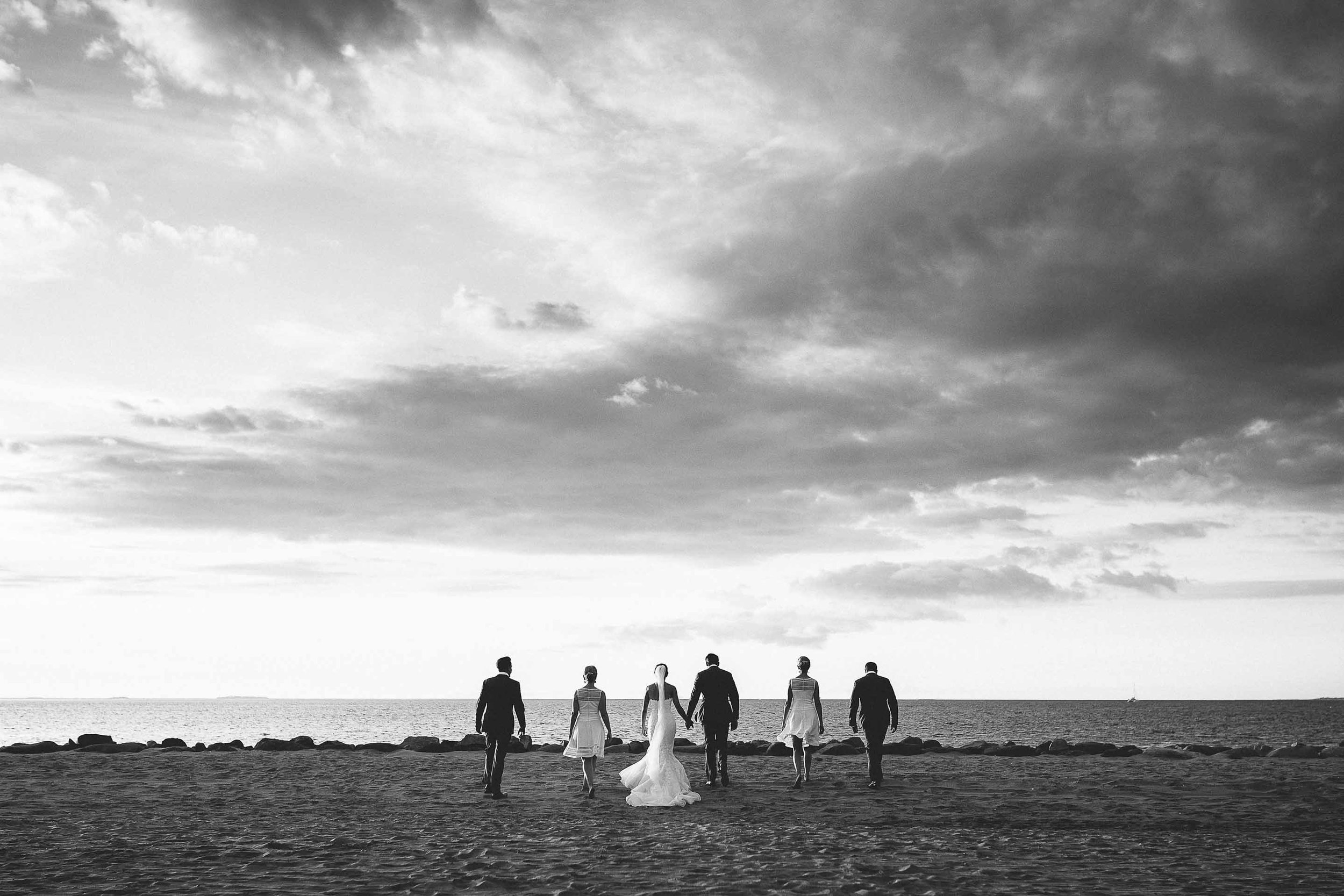 Black and white dramatic image of the bridal party walking towards the ocean on the beach.