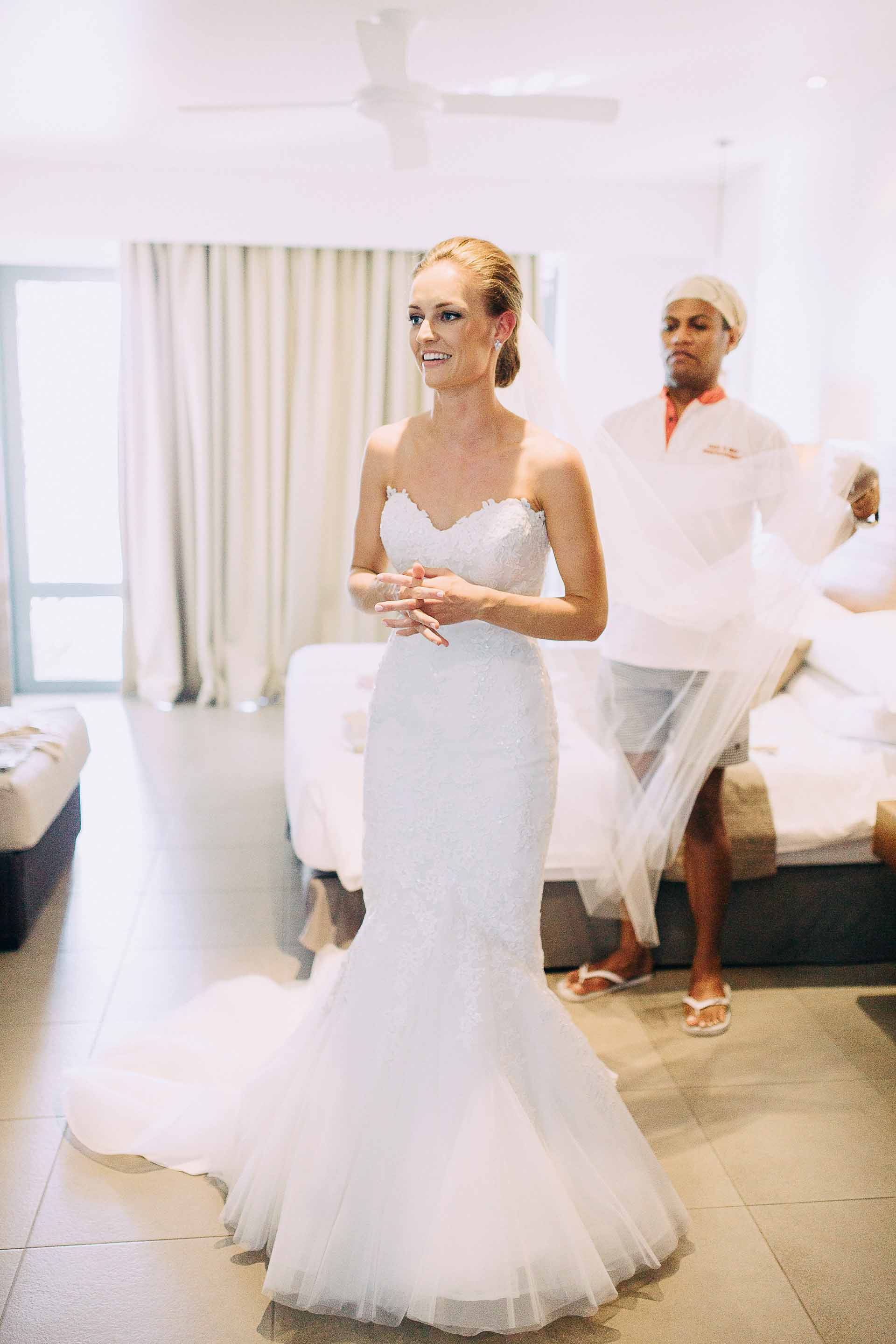 Makeup artist helps the Bride with her beautiful long veil