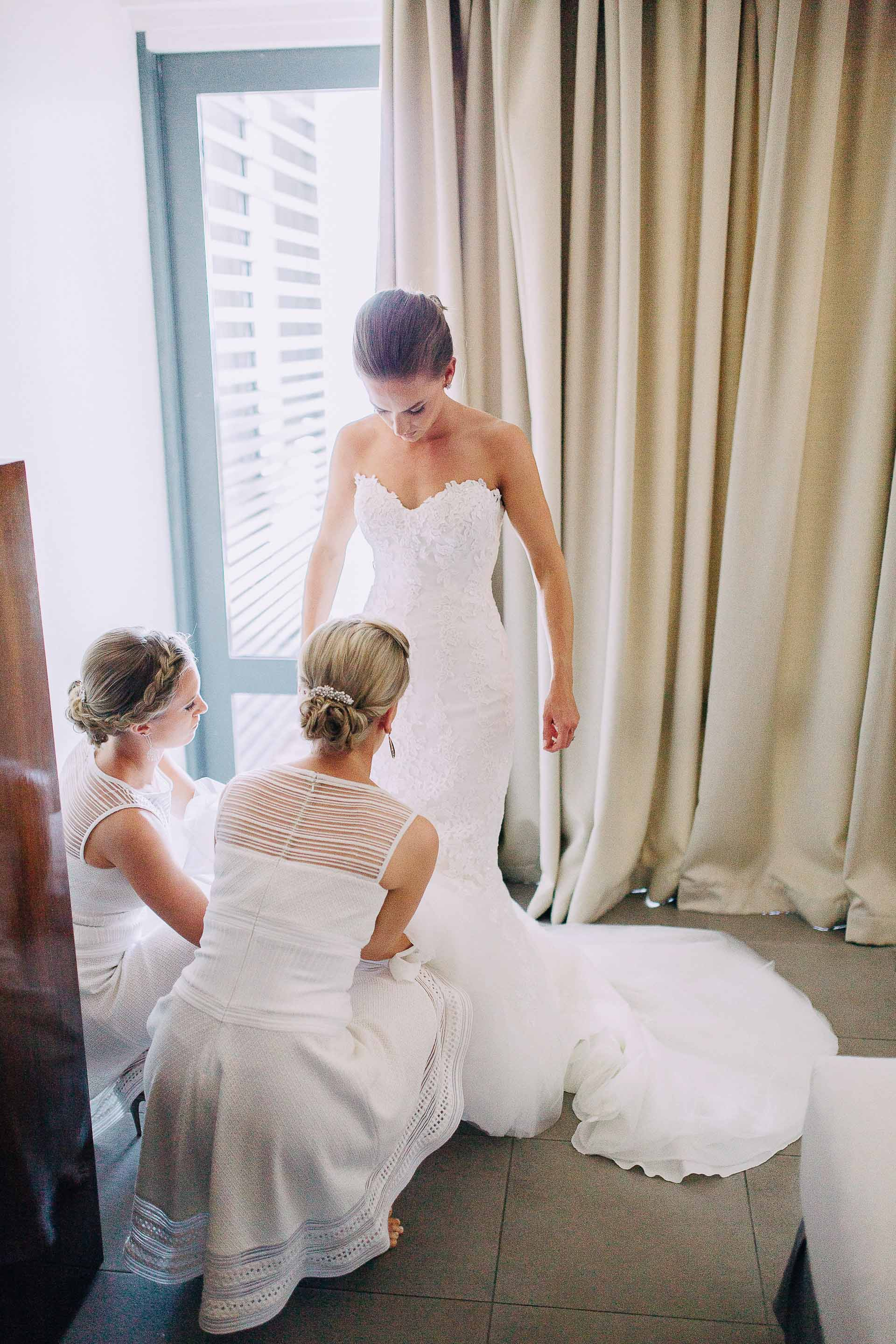 Bridesmaids help the Bride with her wedding dress.