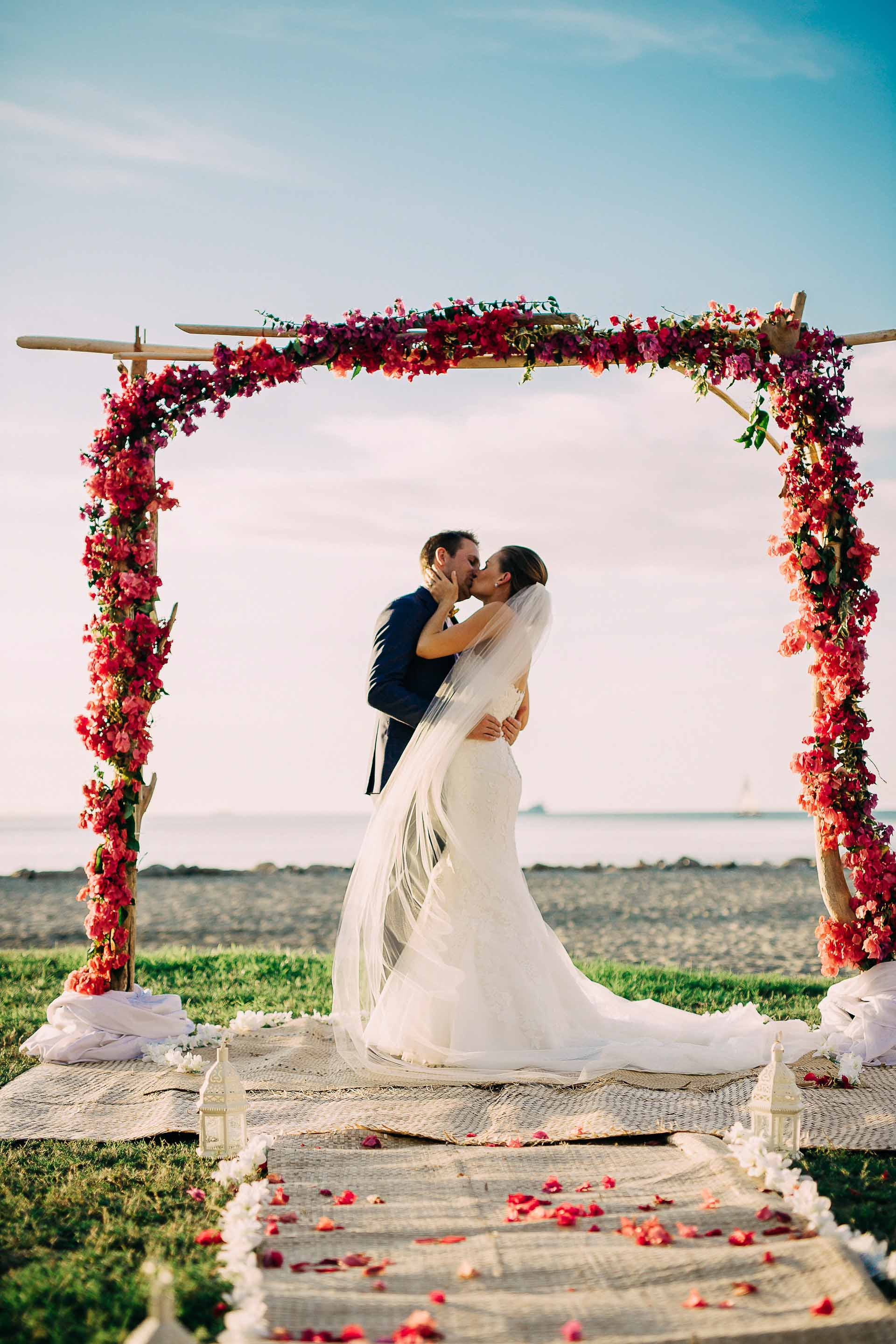 Fiji bride and groom kiss under their beautiful red bougainvillea and drift wood arch after their beach wedding.
