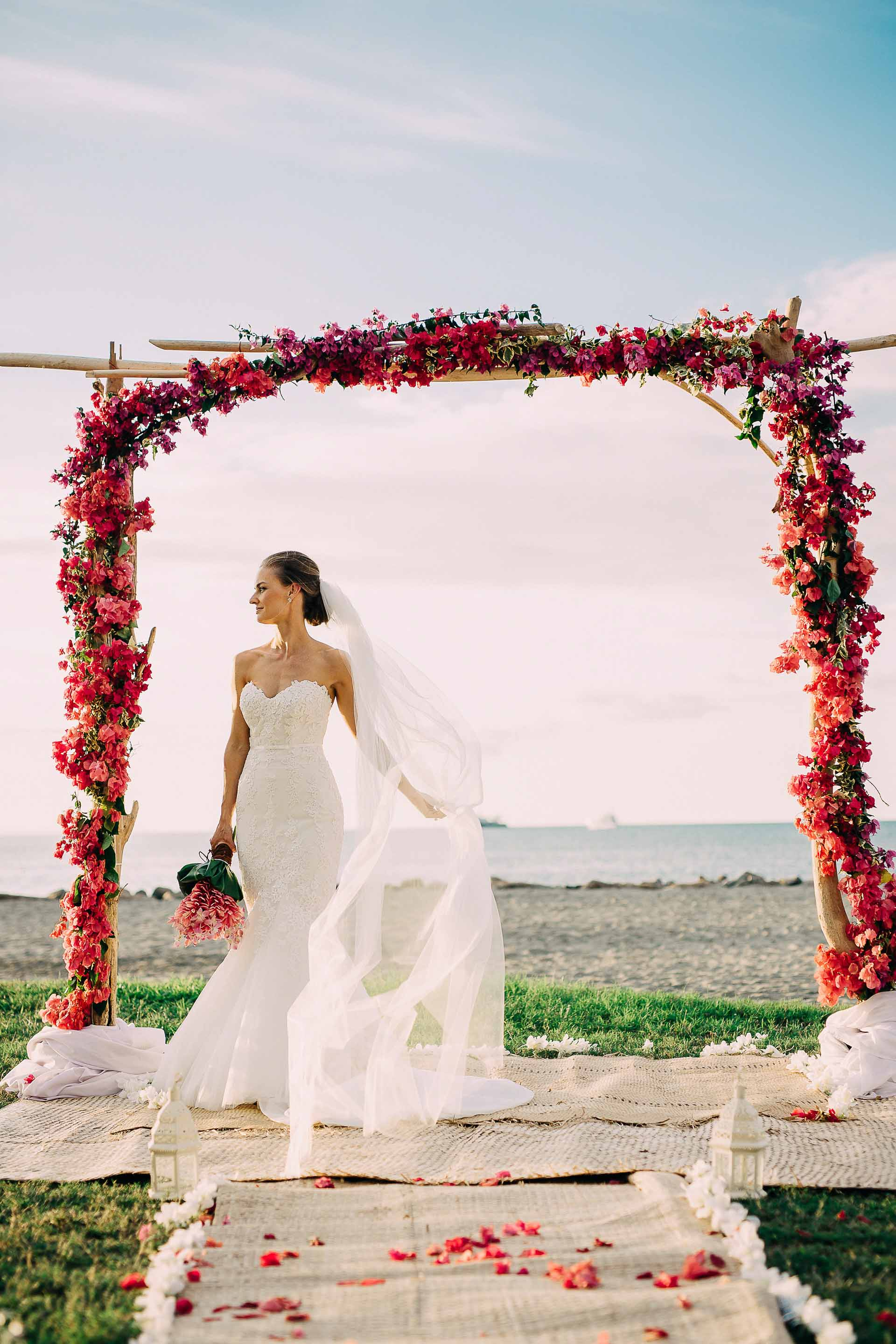 Fiji Bride under her beautiful red bougainvillea and drift wood arch after her tropical beach wedding.