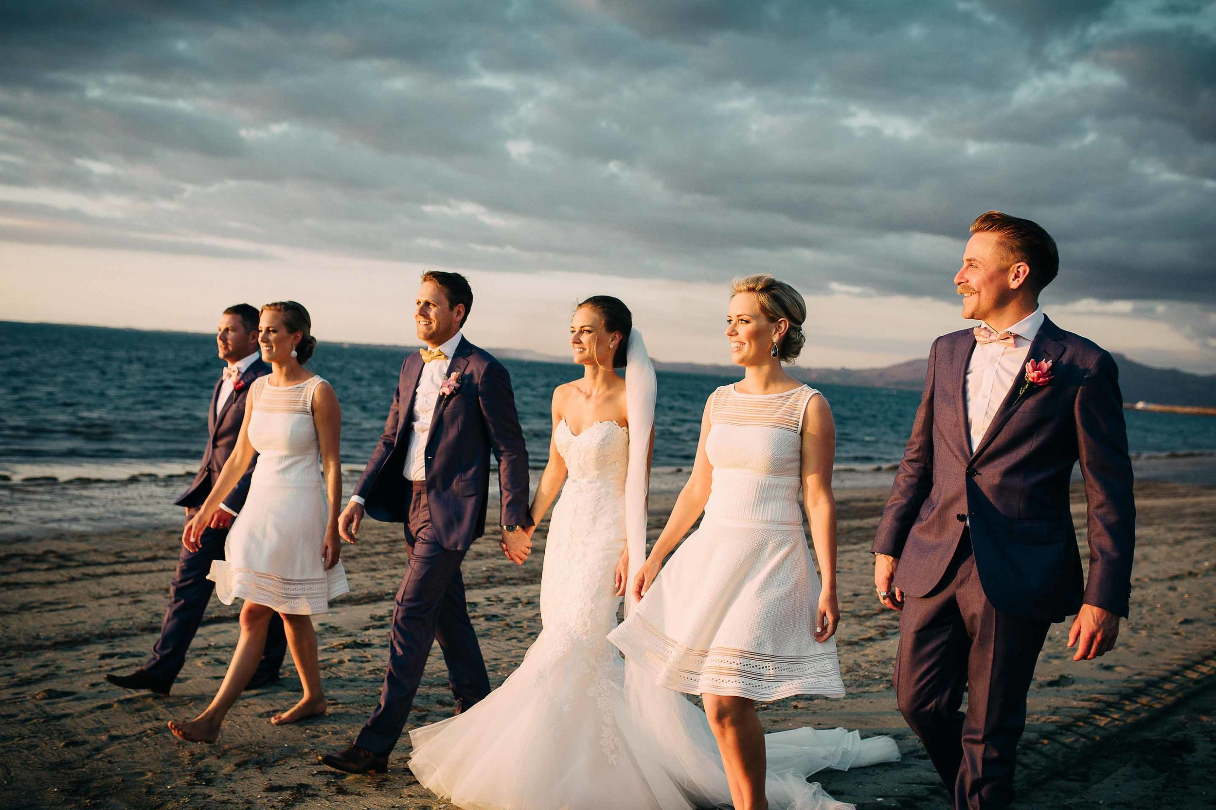 Bride Groom Bridesmaids and Groomsmen enjoy a stroll along the beach at sunset.