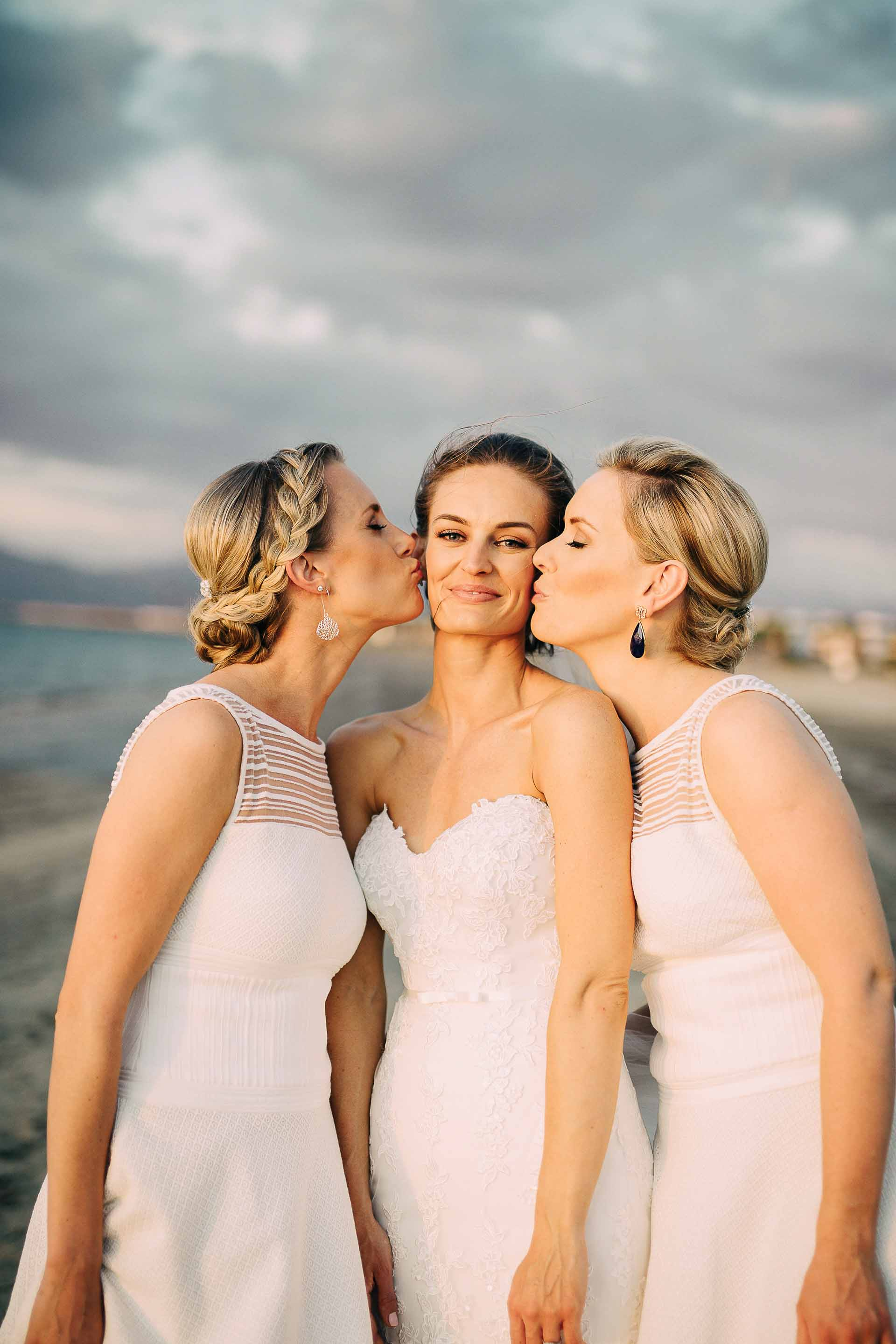Fiji Bridesmaids kiss the Bride's cheeks in a fun girly moment.
