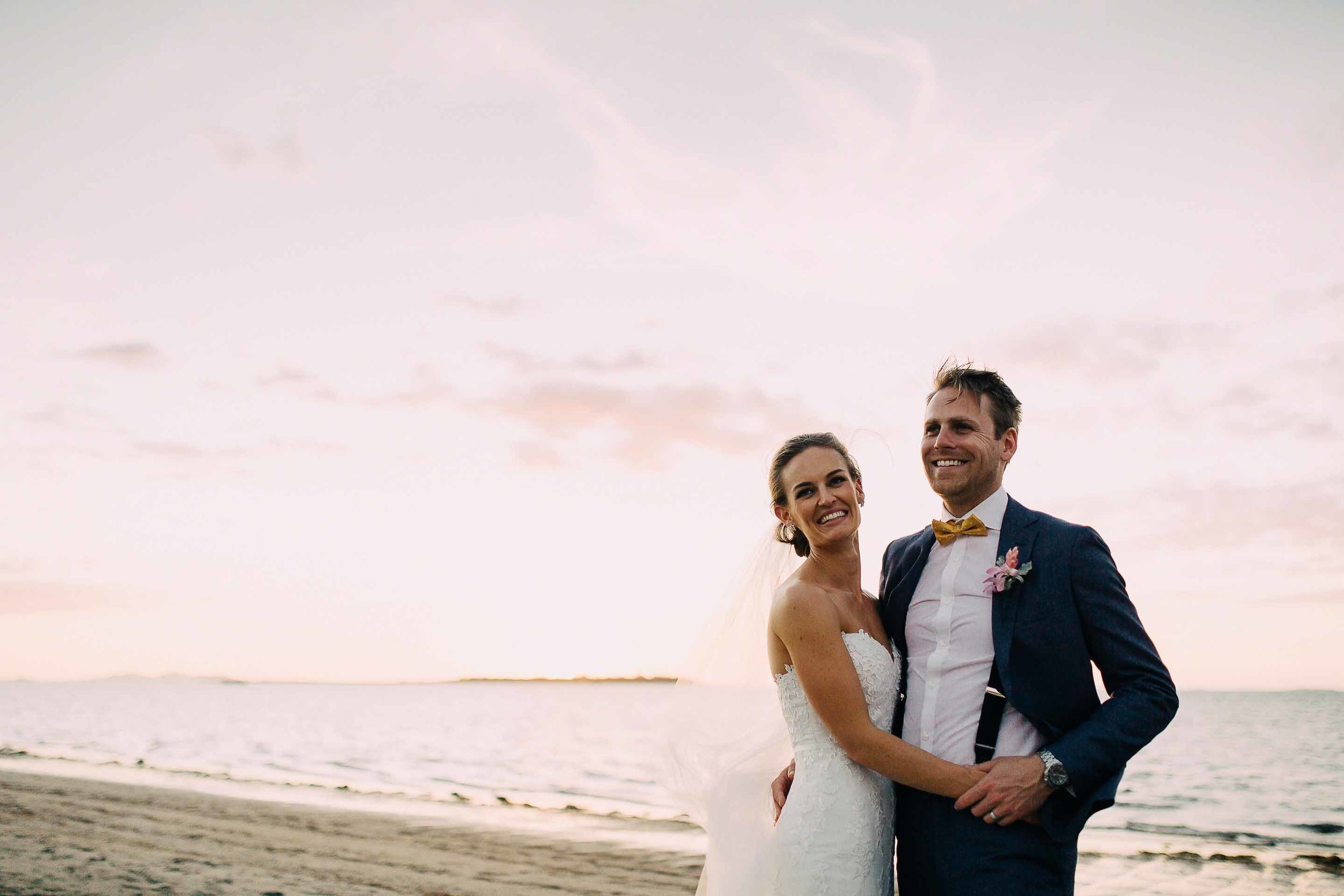 Bride and Groom smile on the beach at sunset.