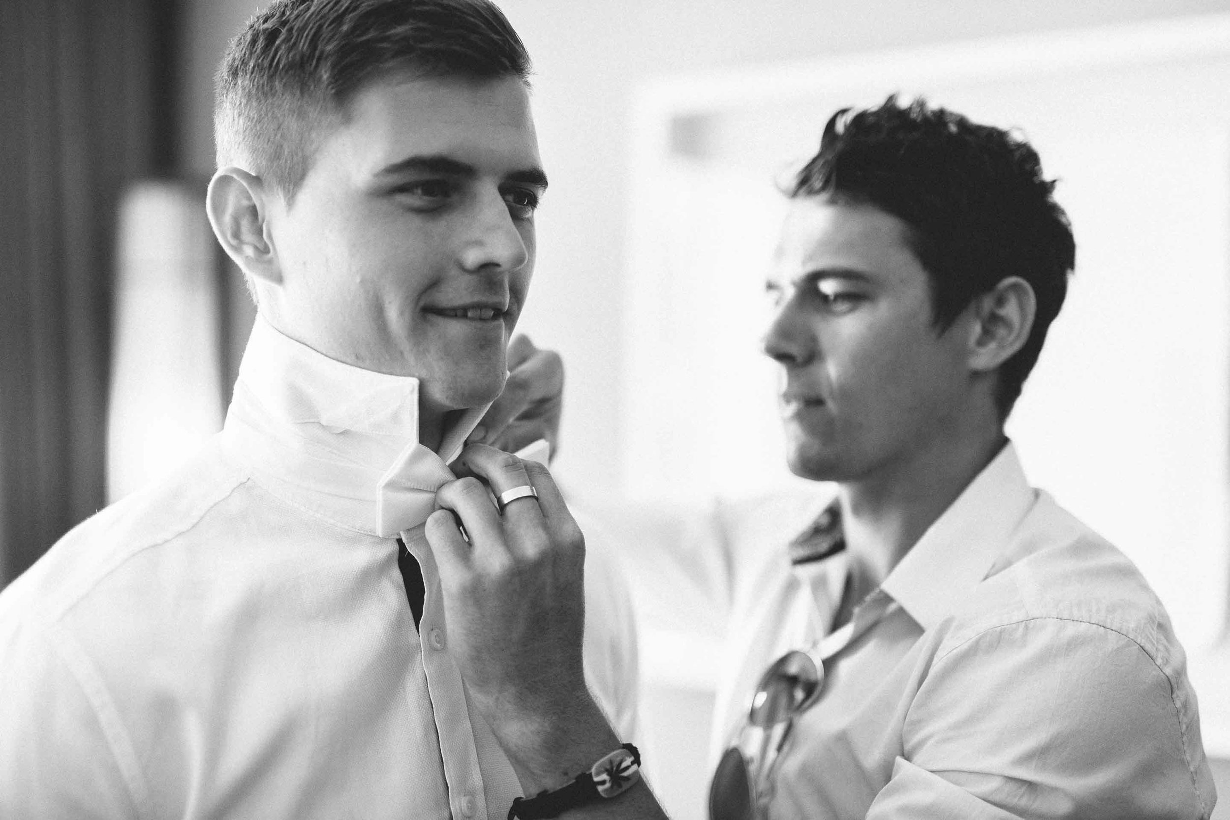 Groomsman helps the excited Groom with his Bow Tie.