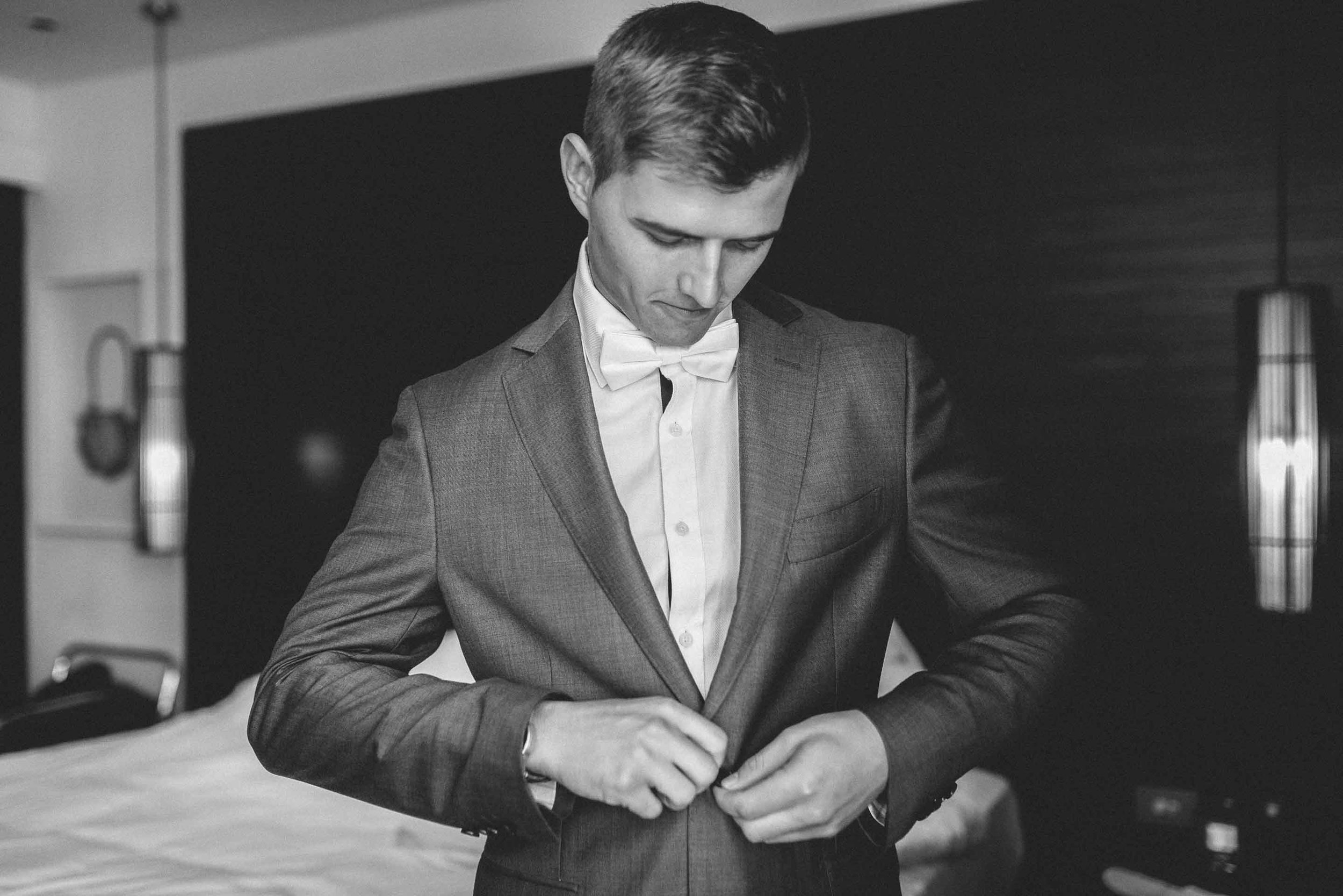 Handsome Groom buttons up his Suit Jacket.