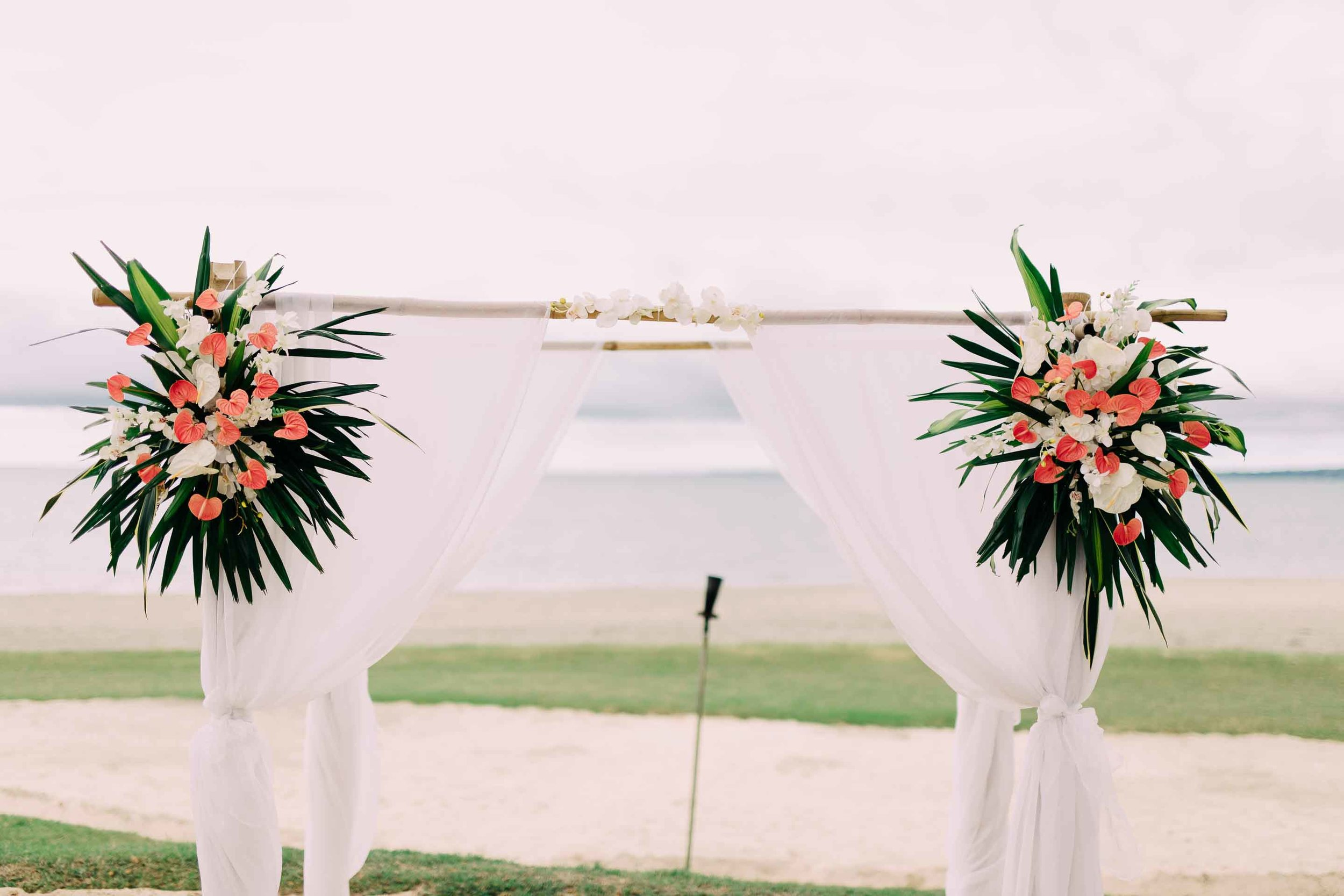 Beautiful tropical colourful flowers on a white draped bamboo wedding ceremony arch. Perfect for a Fiji beach wedding