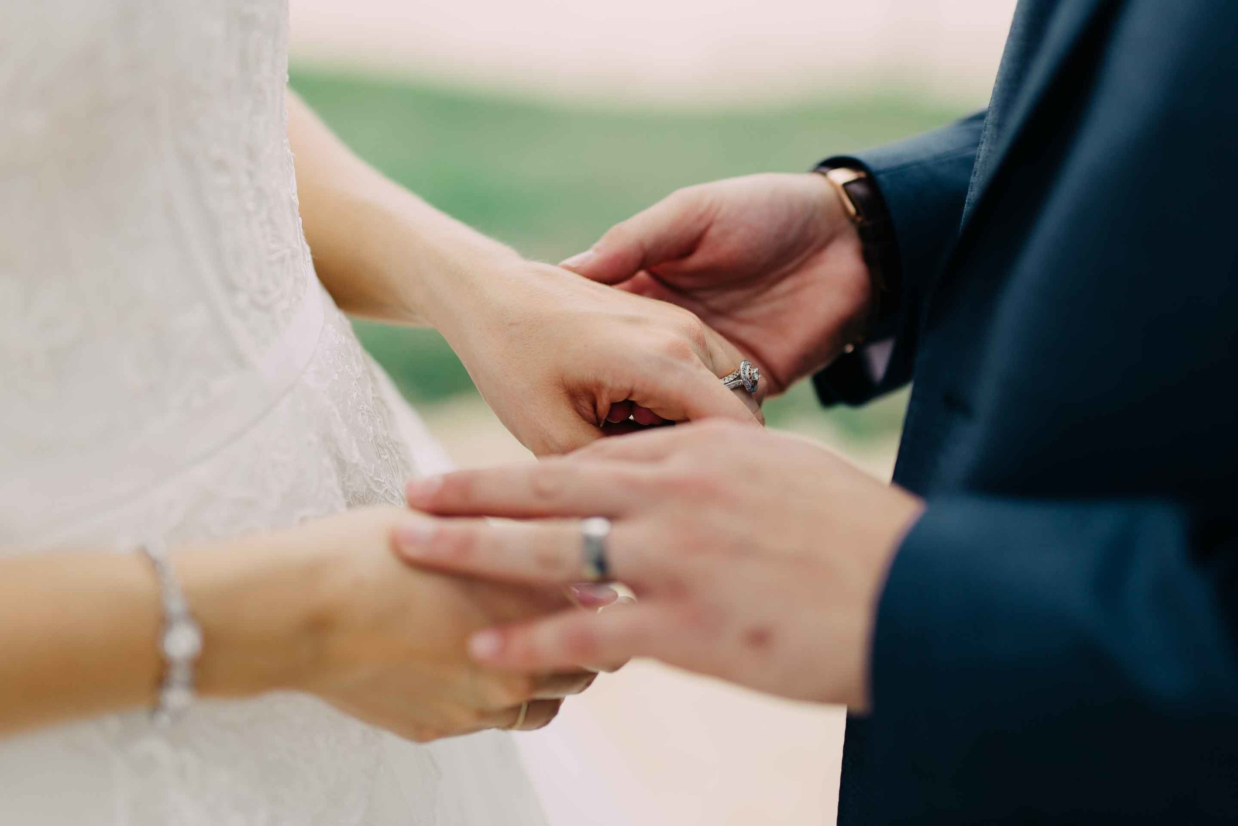 Newlyweds husband and wife hold hands and admire their rings after the marriage.