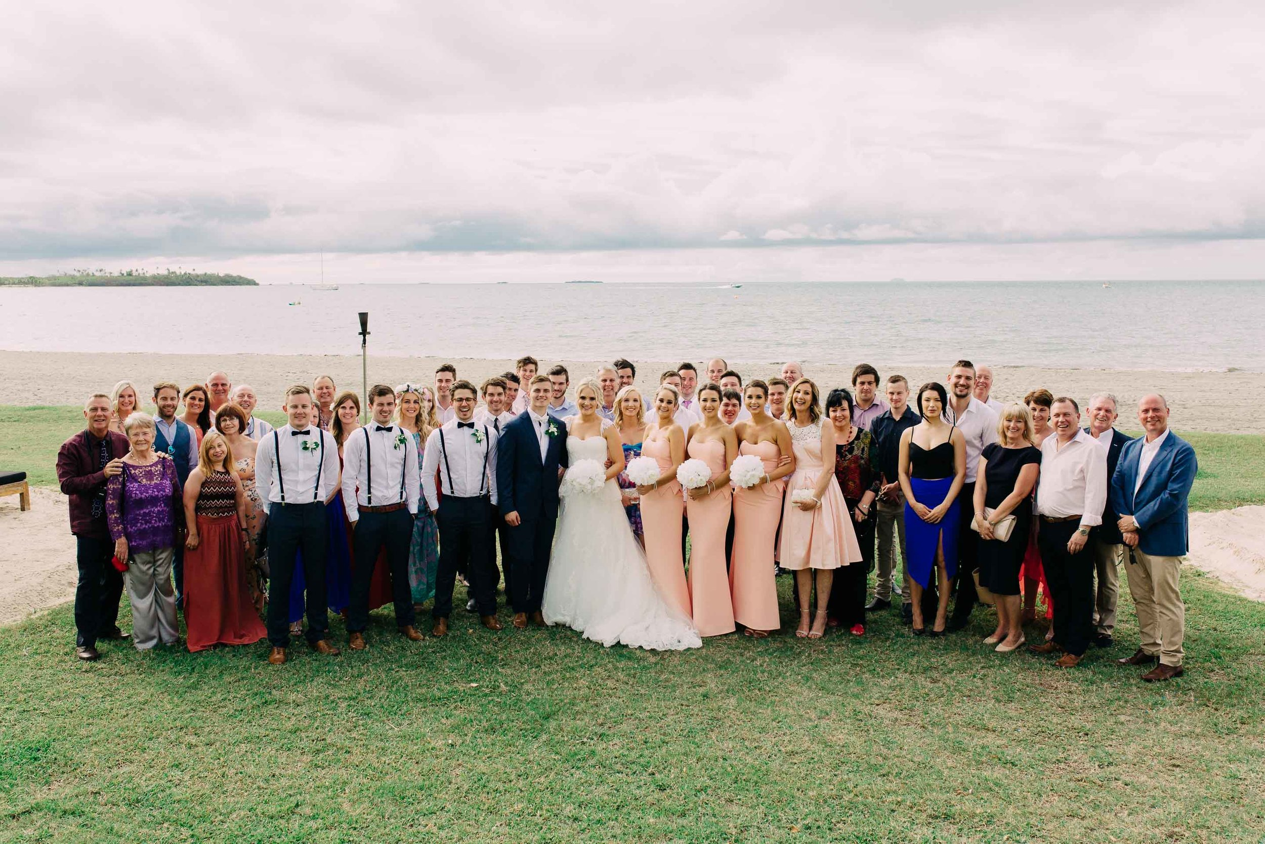 Entire wedding party gather for a group photo after the Fiji beach ceremony.