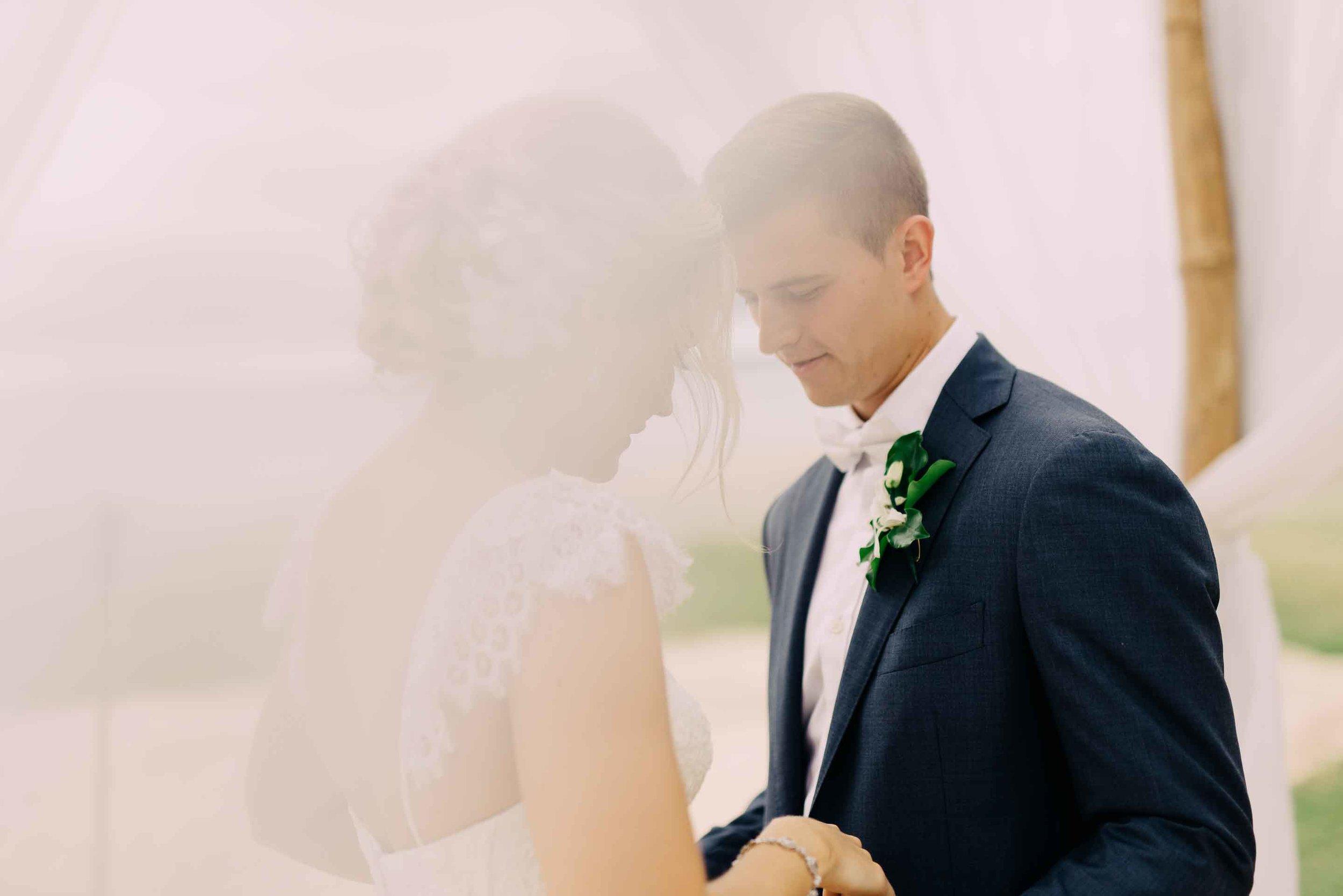 Fiji bride and groom under their white wedding arch.
