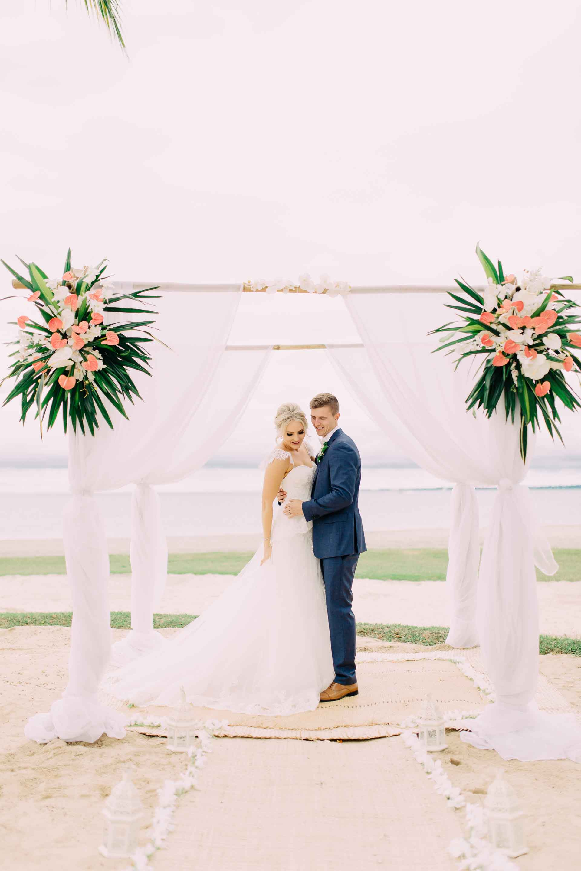 Newlyweds pose with their stunning tropical wedding ceremony arch on the Hilton Fiji Beach.
