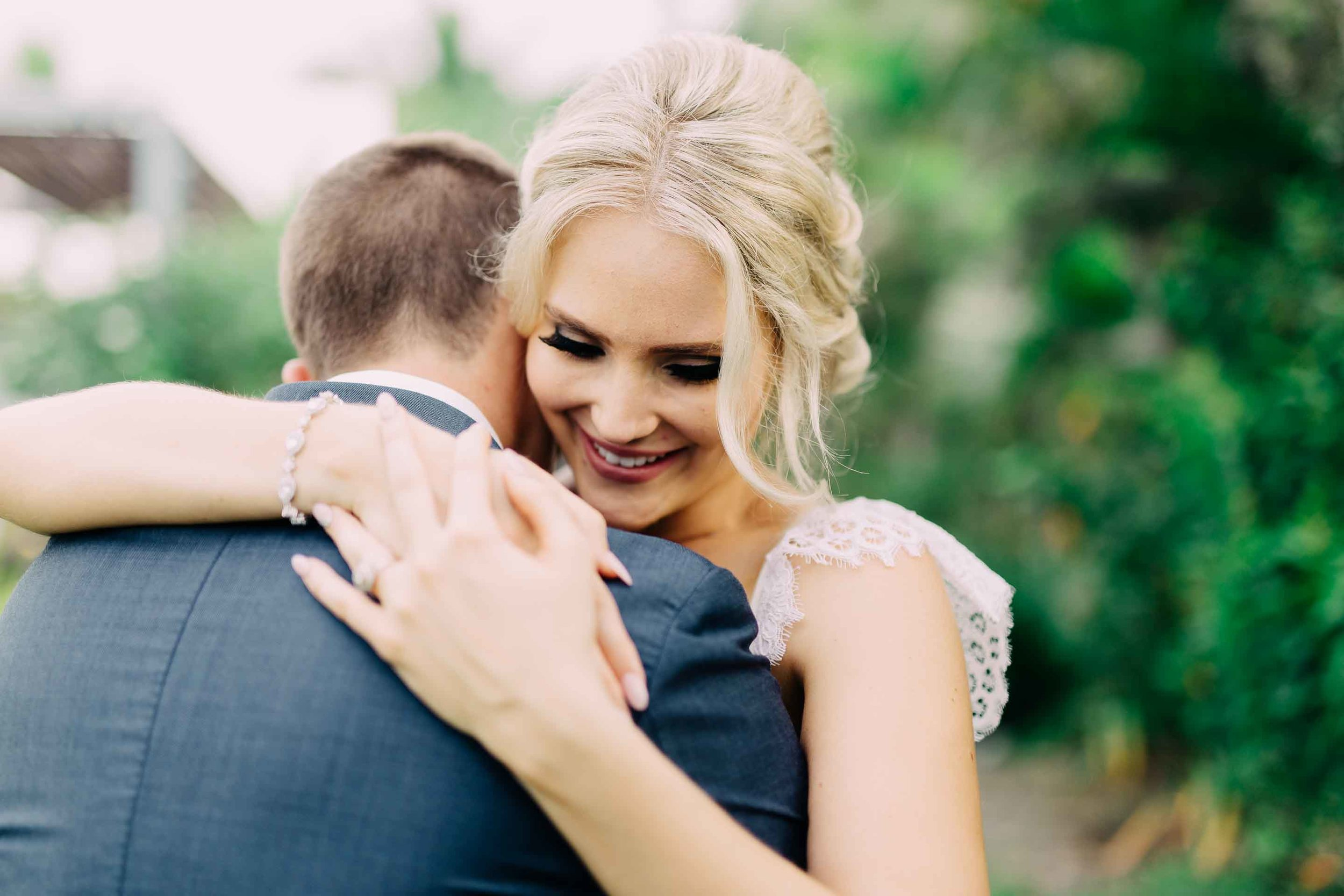 A cute moment between the newlyweds smily bride embraces her new husband.
