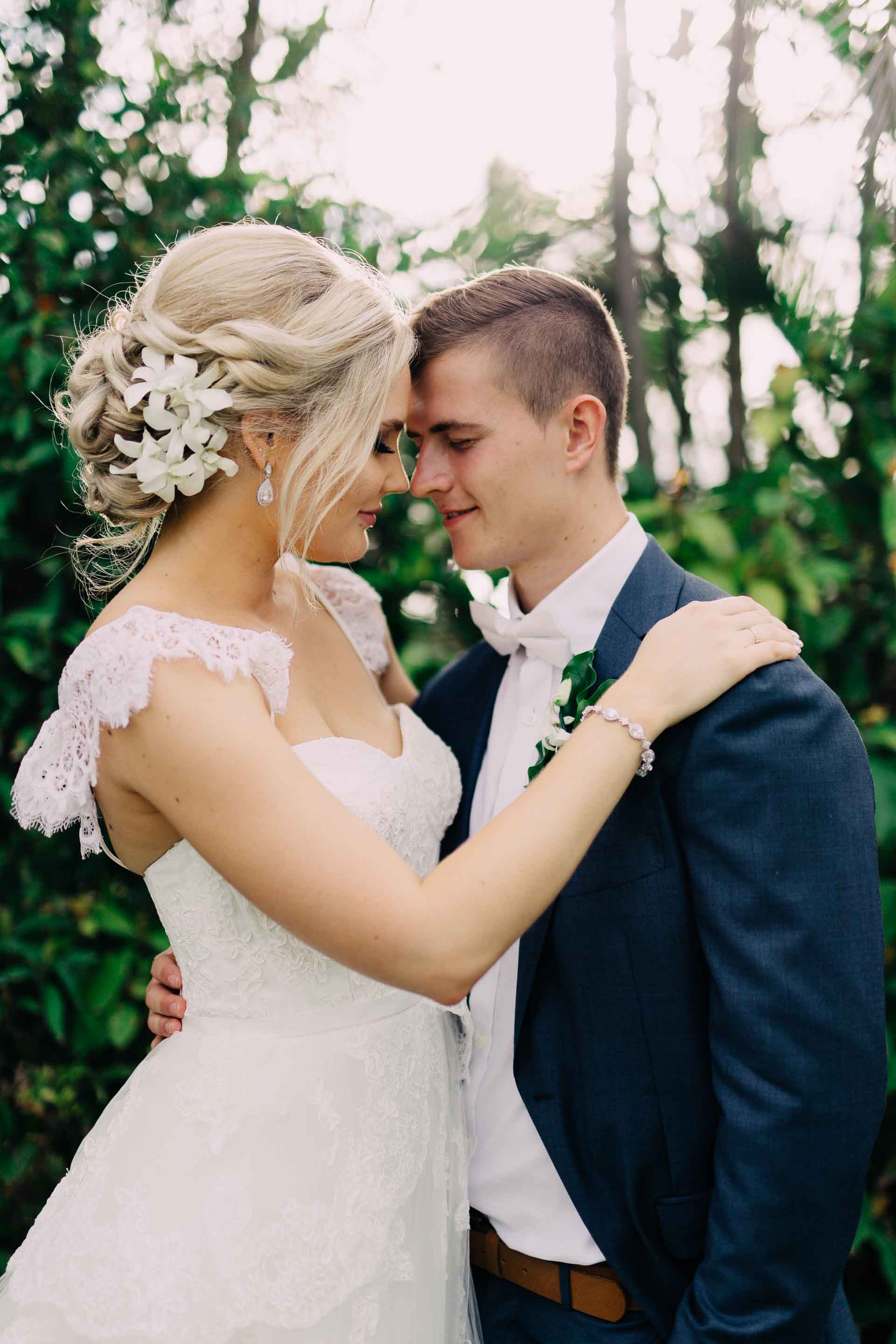 Newlyweds touch foreheads and smile.