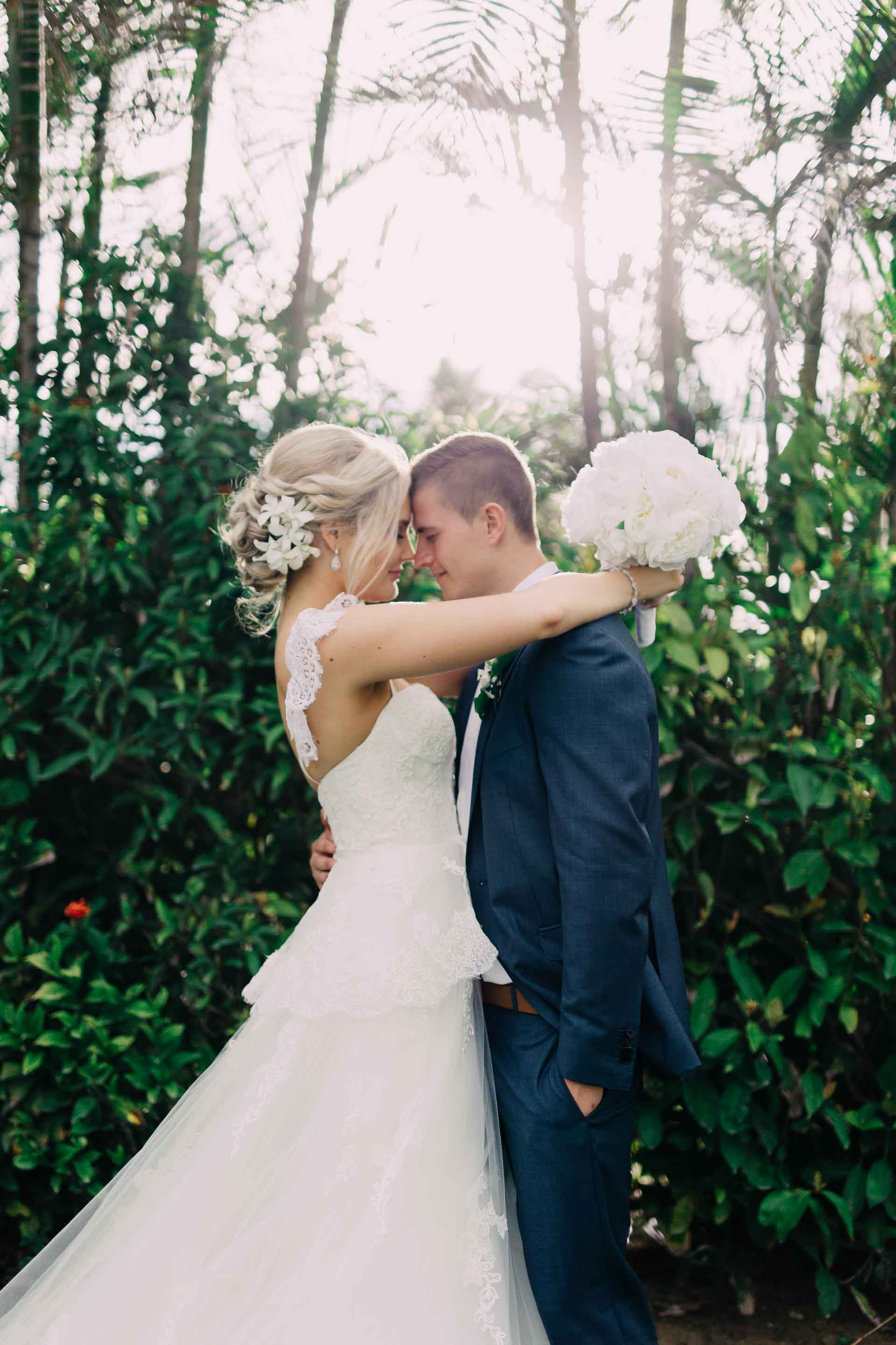 Stunning portrait of bride and groom beautiful white wedding dress and classic blue wedding suit tropical Fiji wedding at the Hilton.