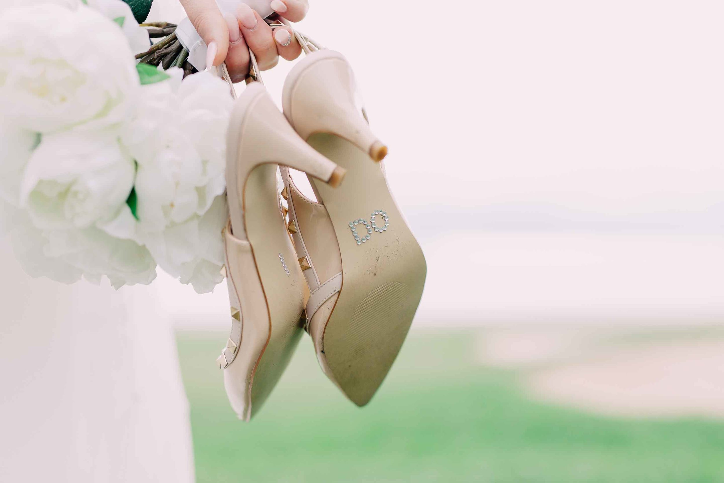 Artificial white peony wedding bouquet and bride's shoes with I Do on the soles in rhinestones. Wedding shoes are Nude Valentino studded heels.