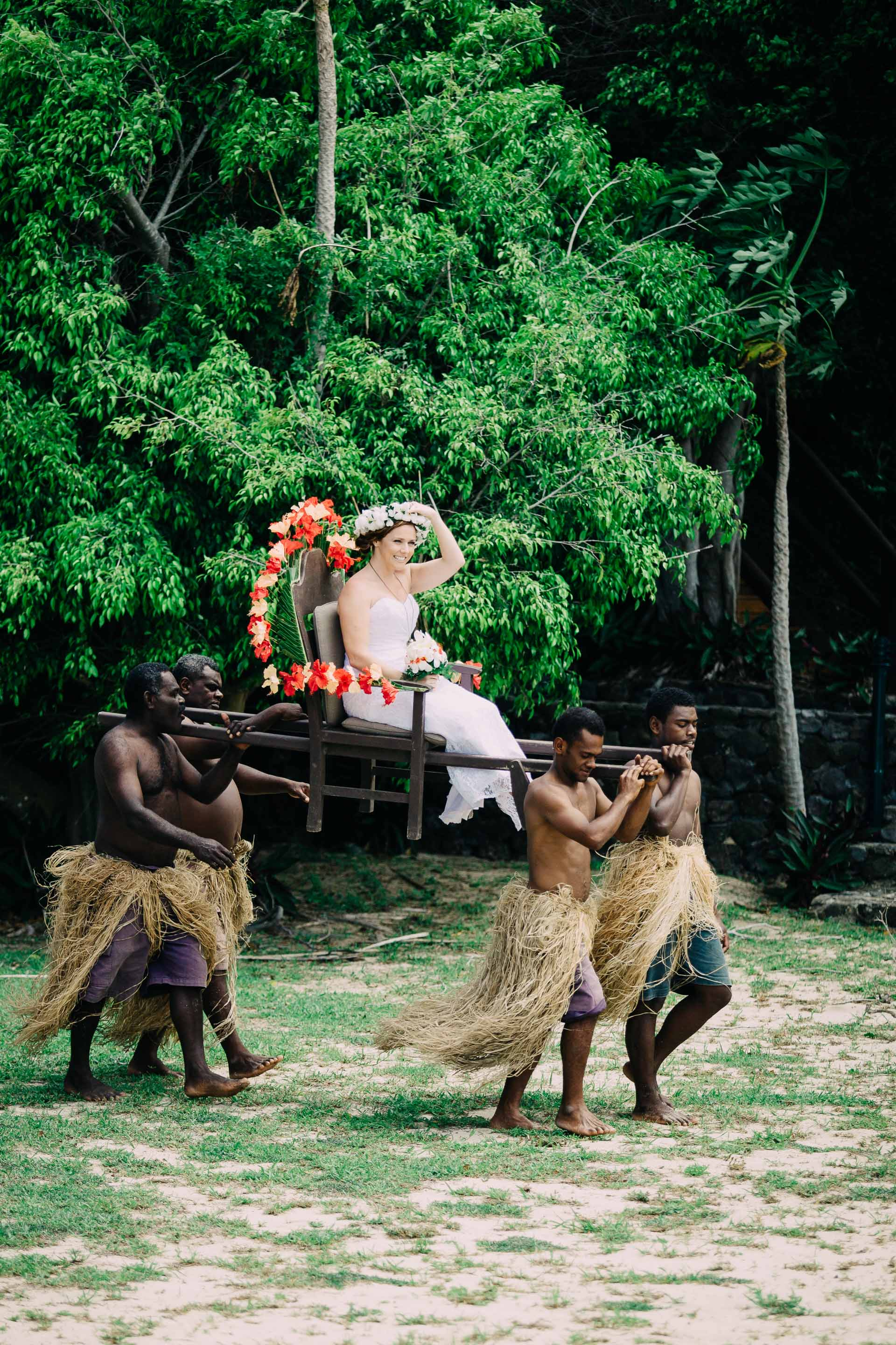 the bride being carried to the altar by Fijian warriors
