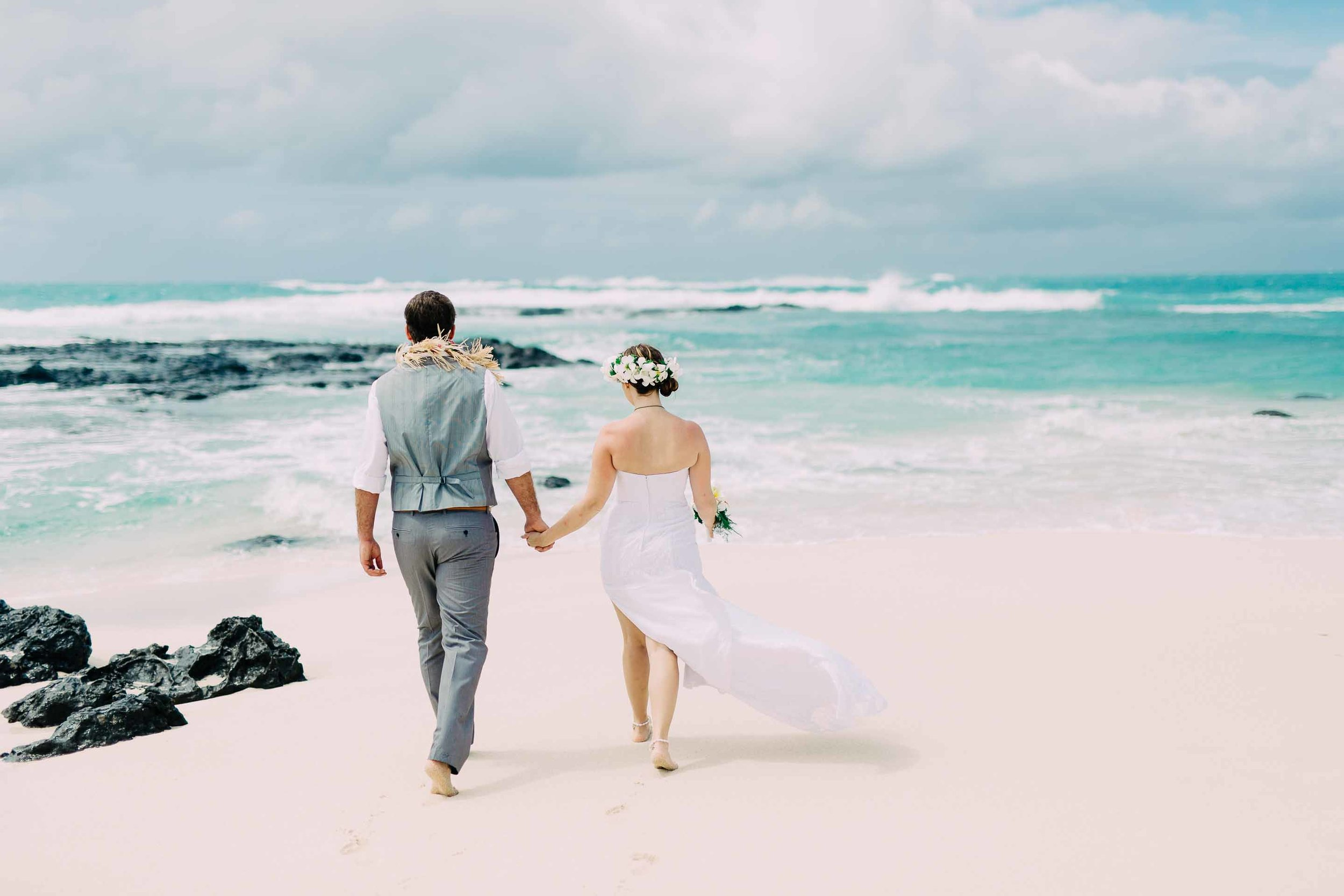 the couple walking towards the rocks with the brides wedding dress being blown out by the wind