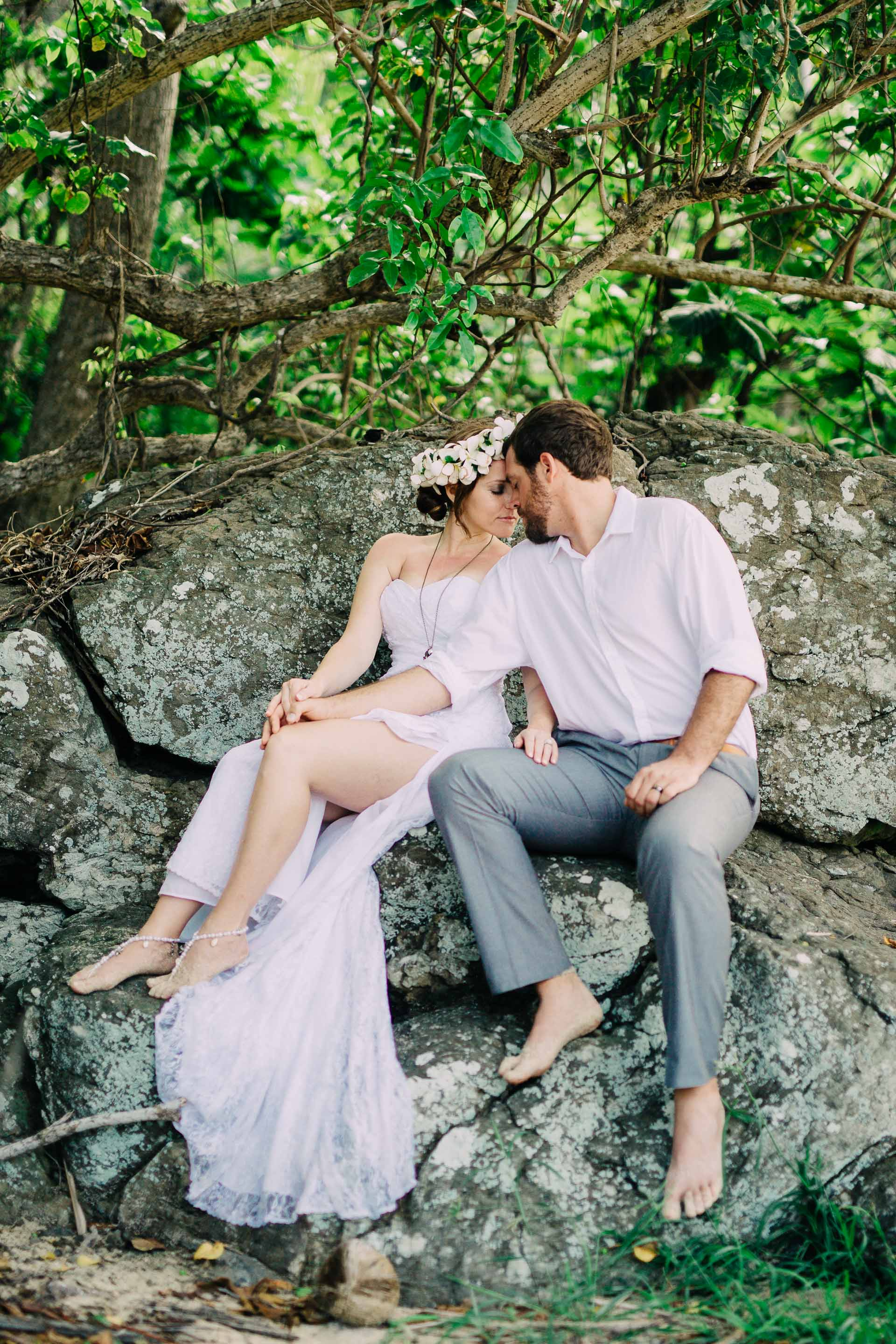 The newlyweds sitting on a rock together in the bush