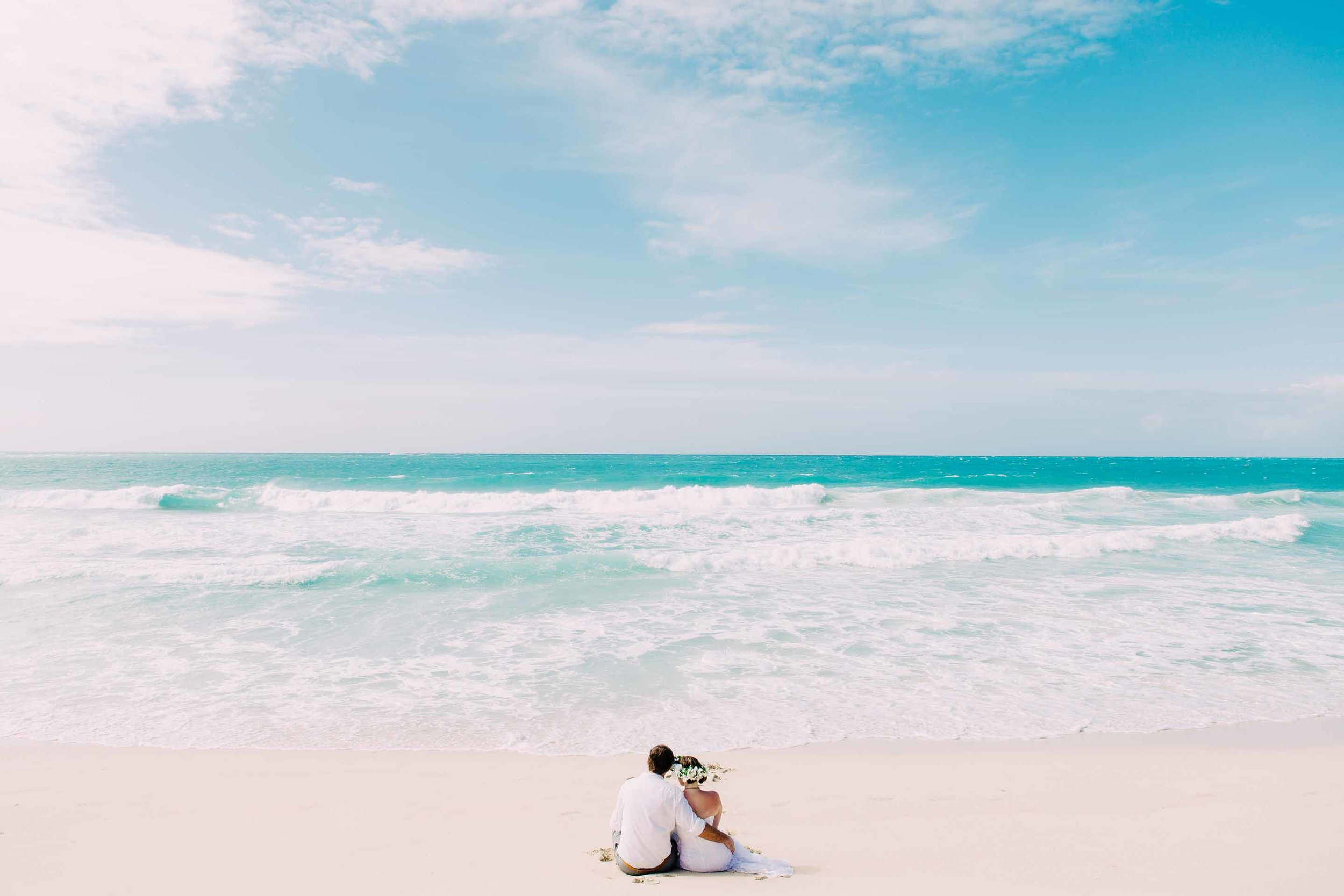 the couple sitting alone on the deserted beach