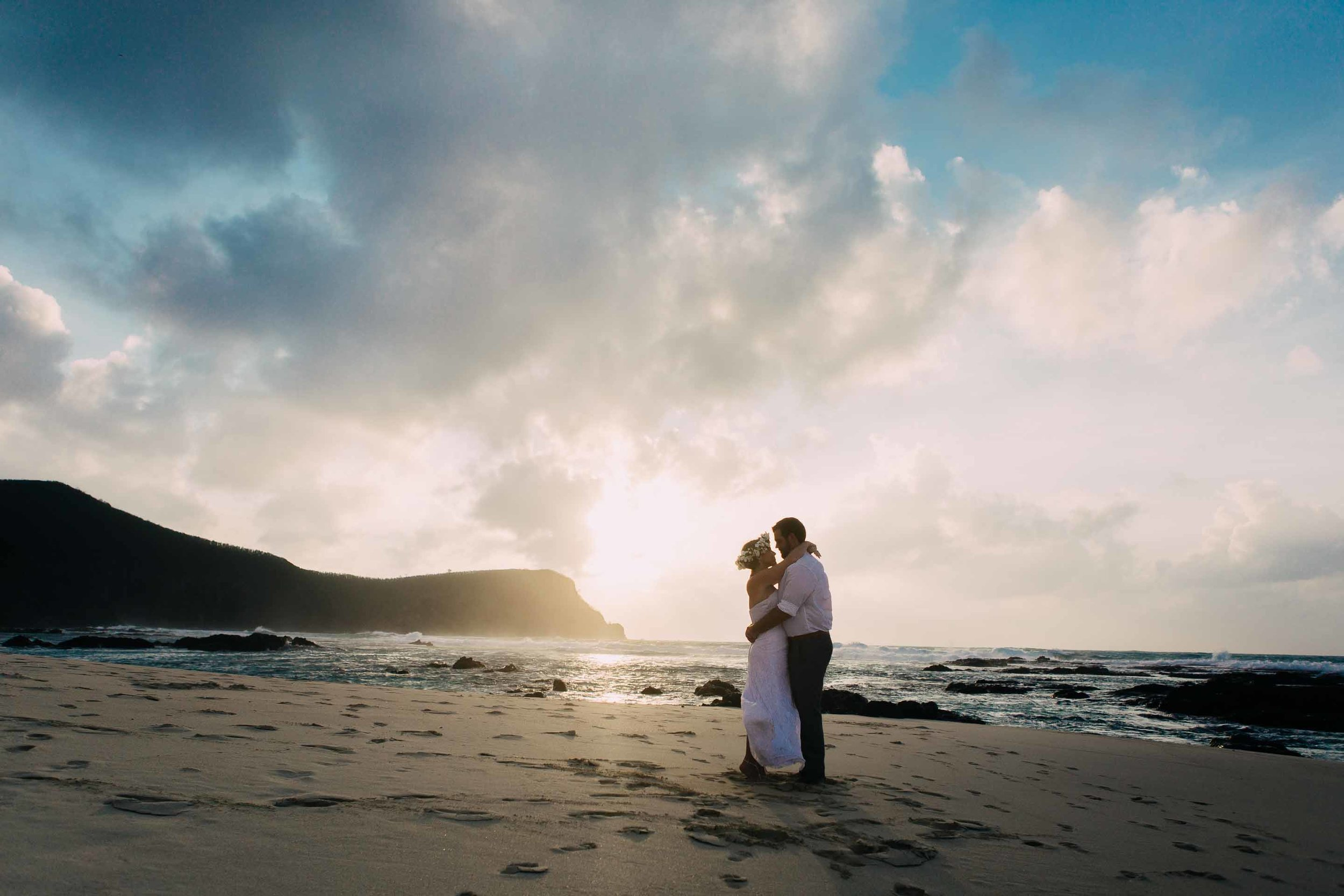 the couple on the beach with sunset behind them