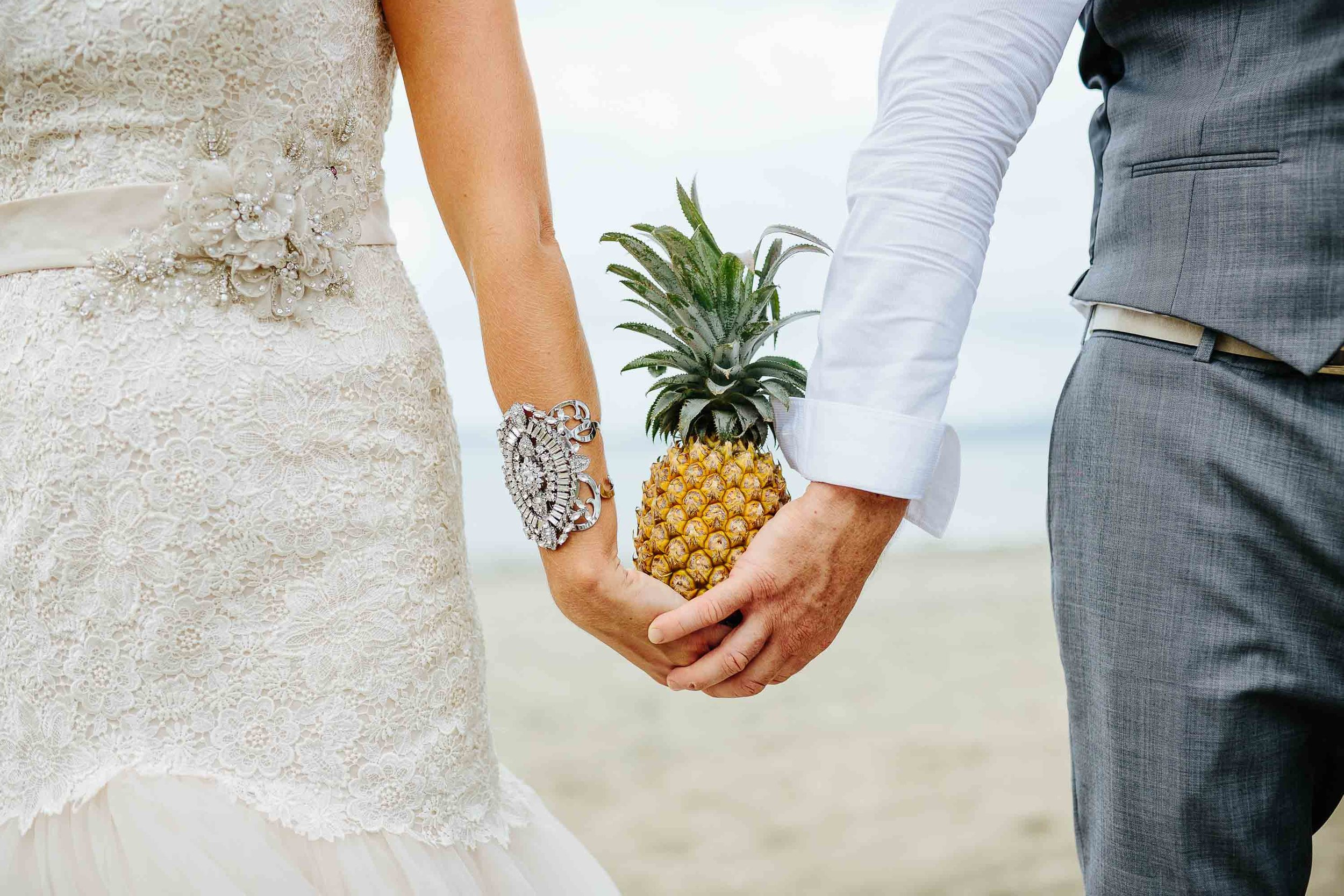 the couple holding a pineapple between them