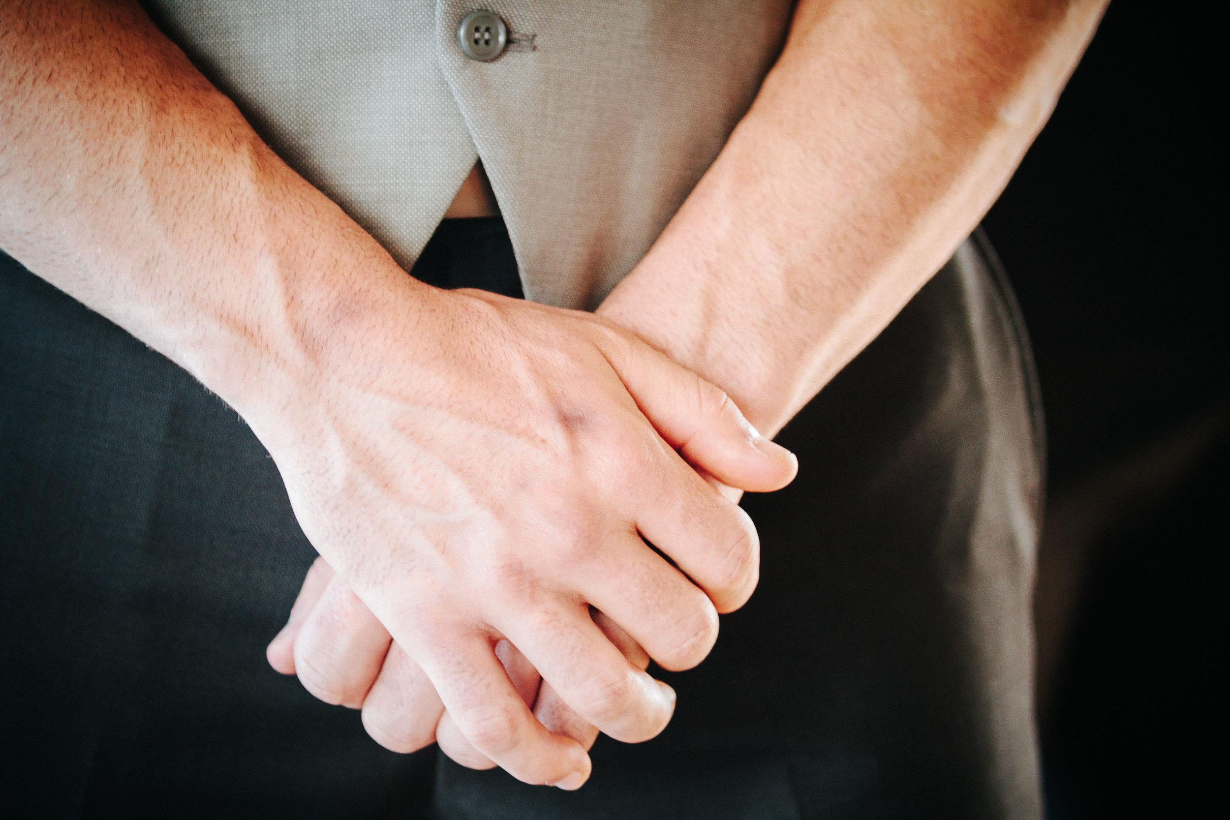 groom crossed hands waiting nervously