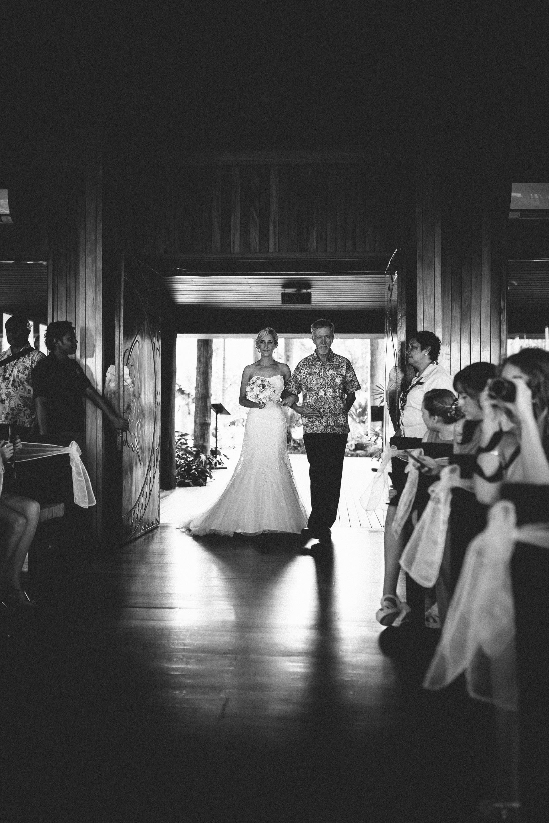 Bride being walked down the aisle by her father, black and white