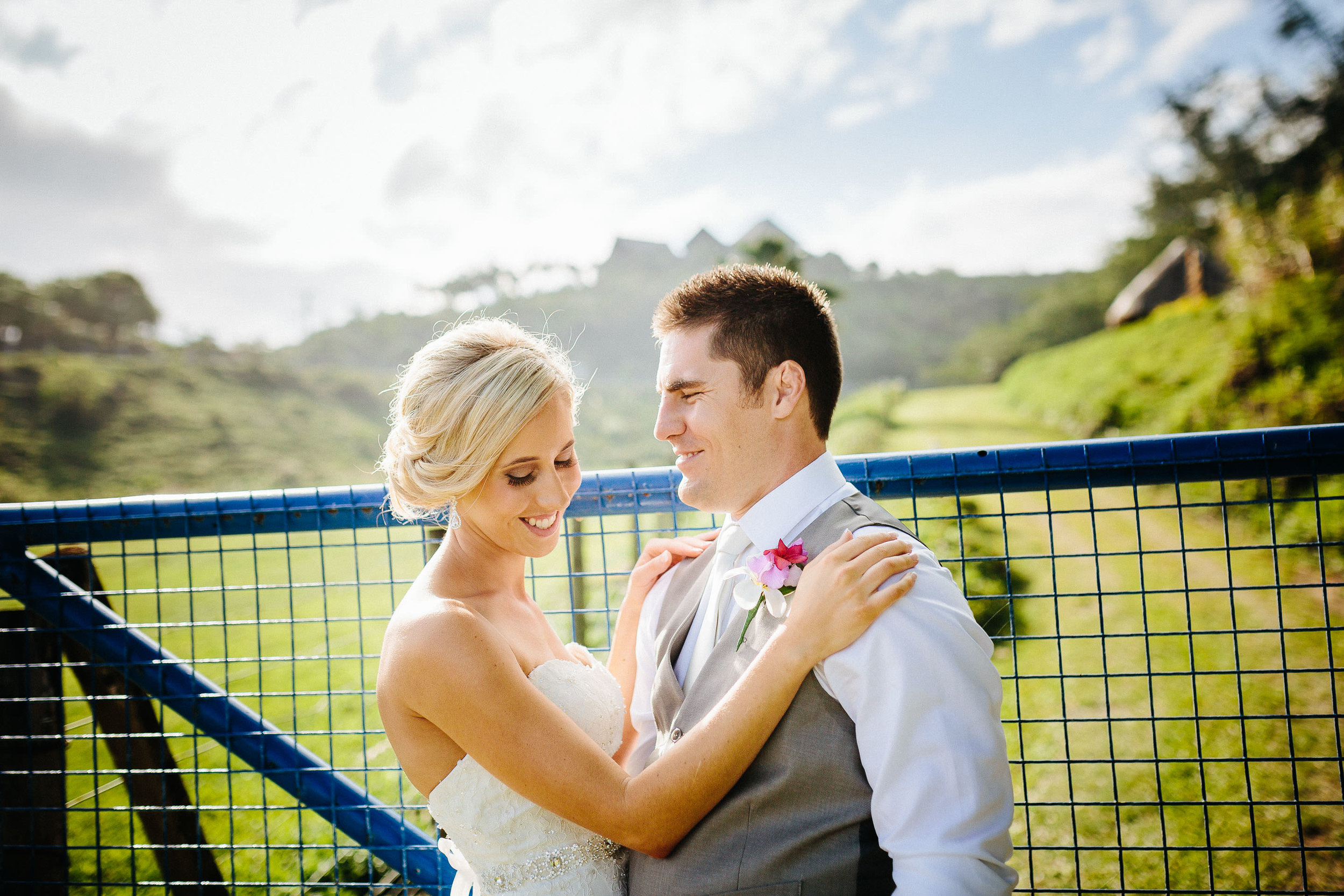bride and groom against a blue gate