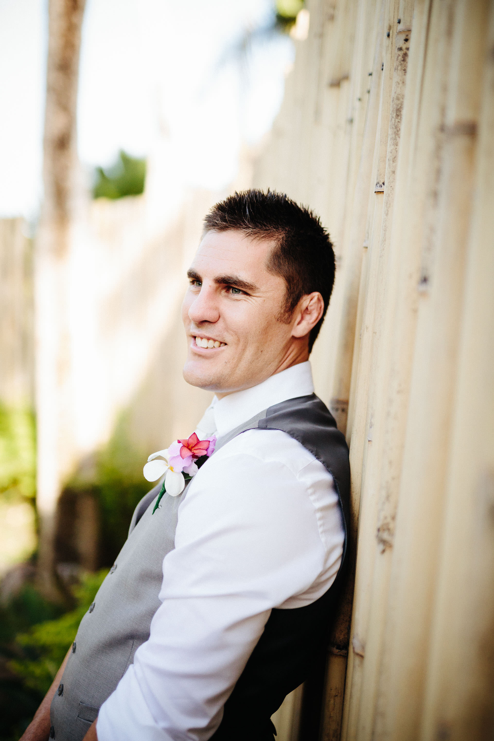 groom leaning against bamboo fence