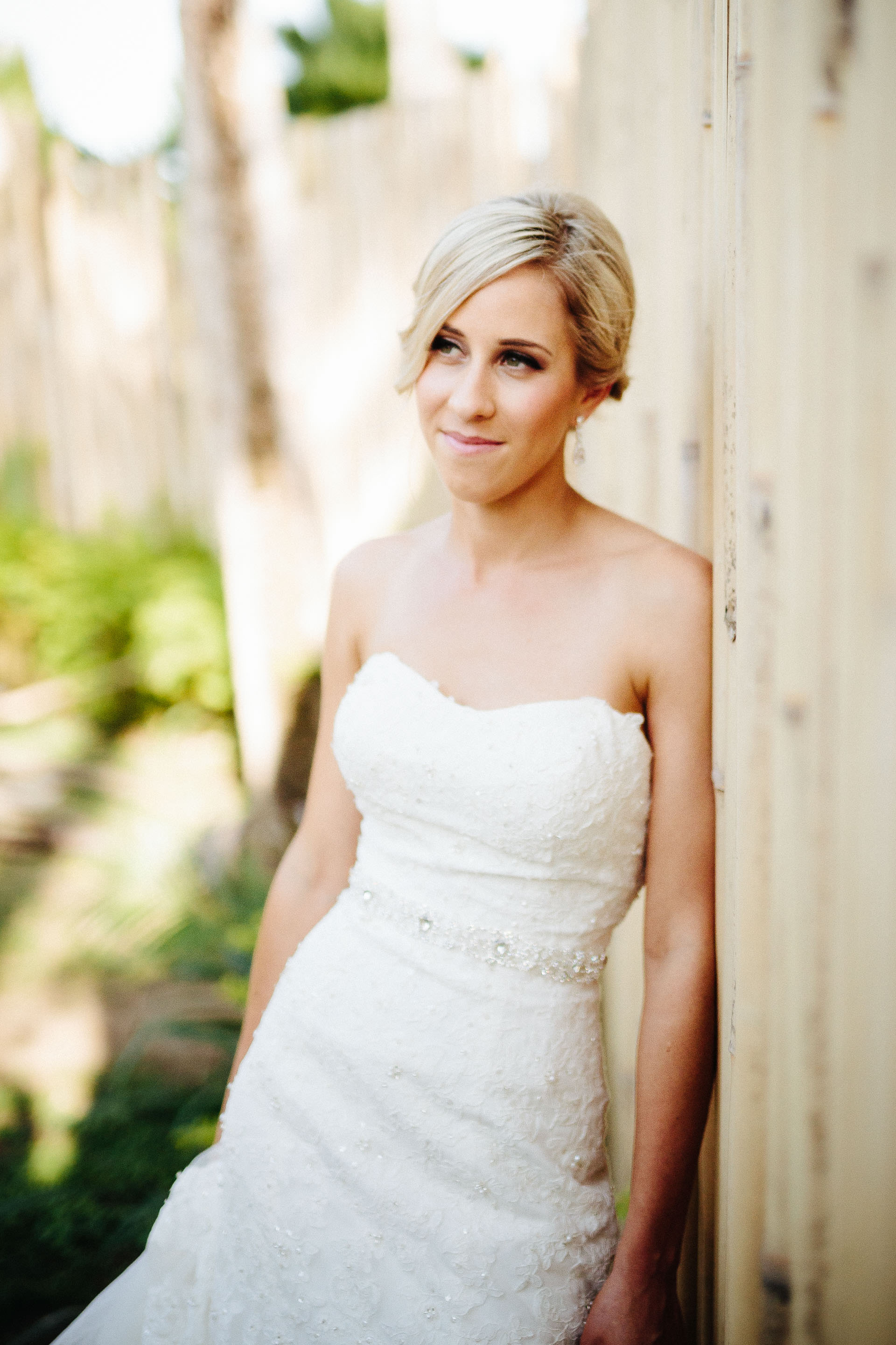 bride leaning against bamboo fence
