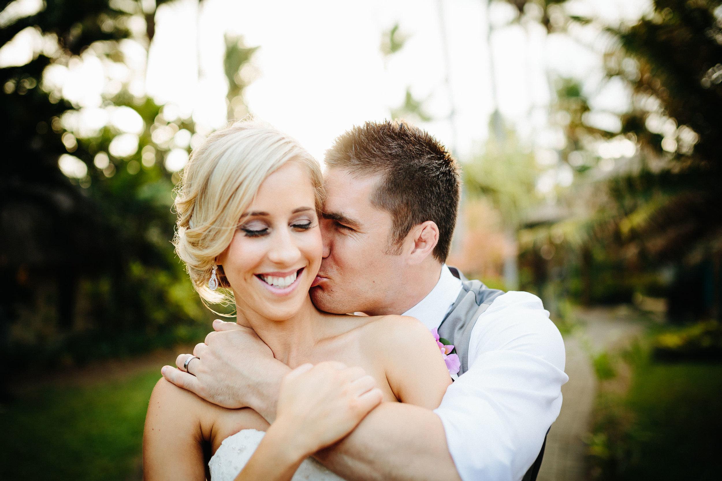 groom kissing bride on her neck