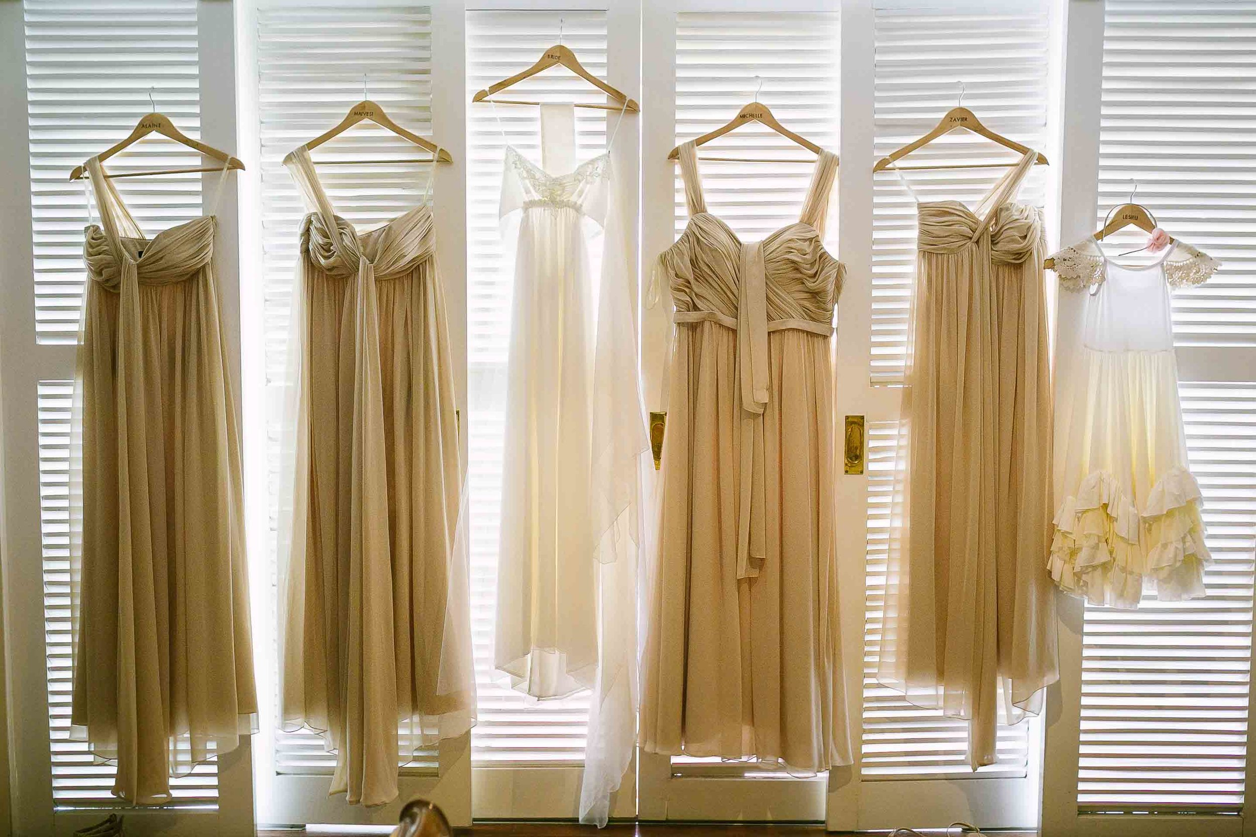 wedding gown and bridesmaid dresses hung from white shutters