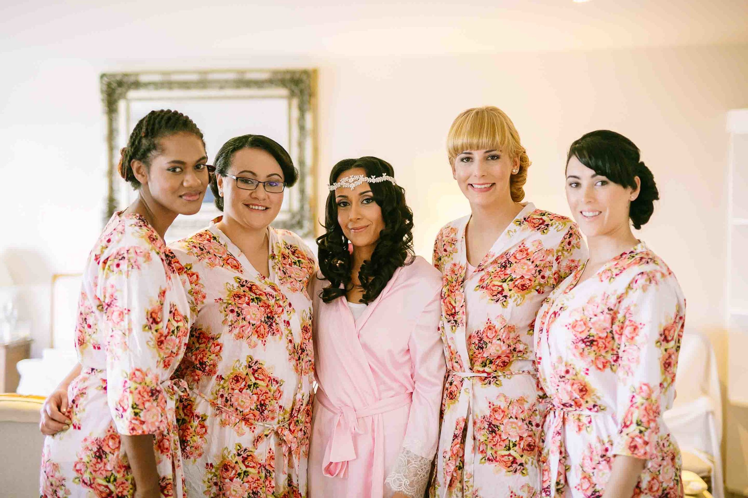 bride with her bridesmaids in their robes
