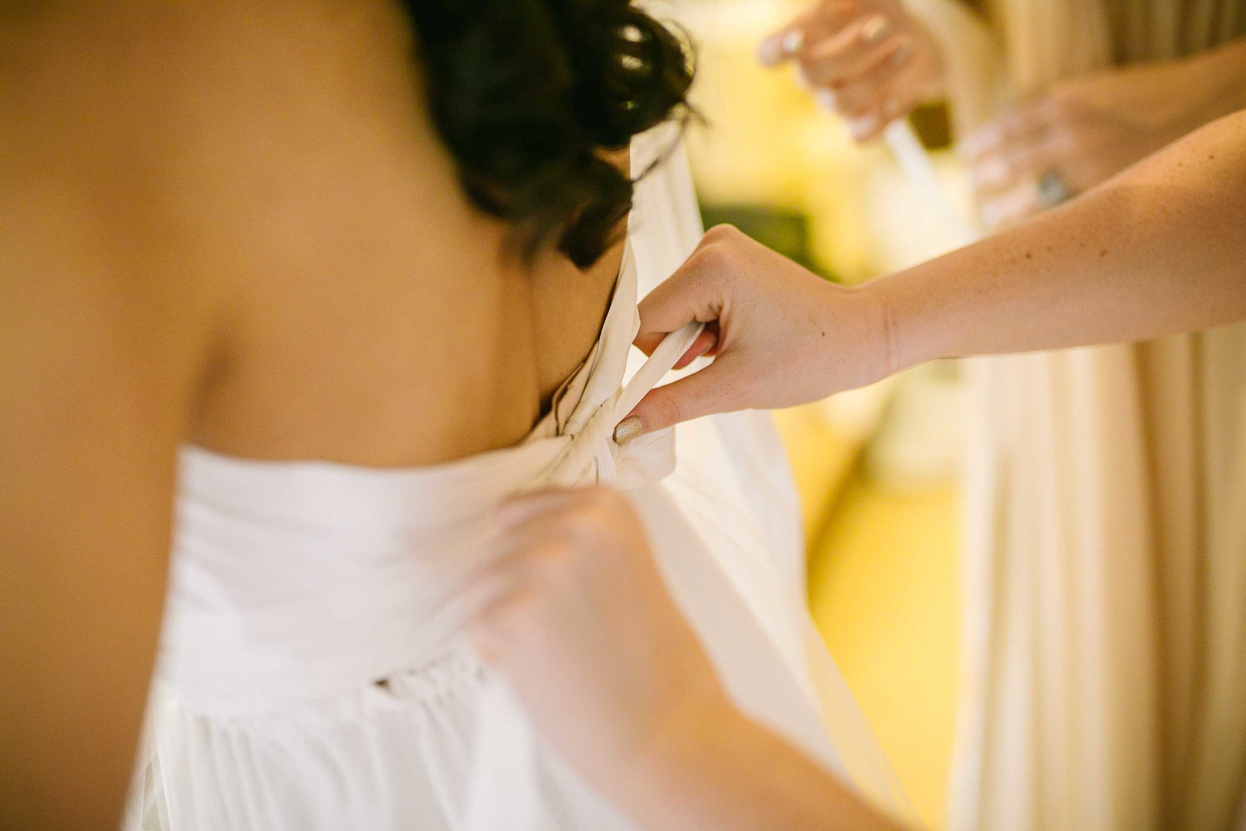 bridesmaids helping the bride into her wedding gown