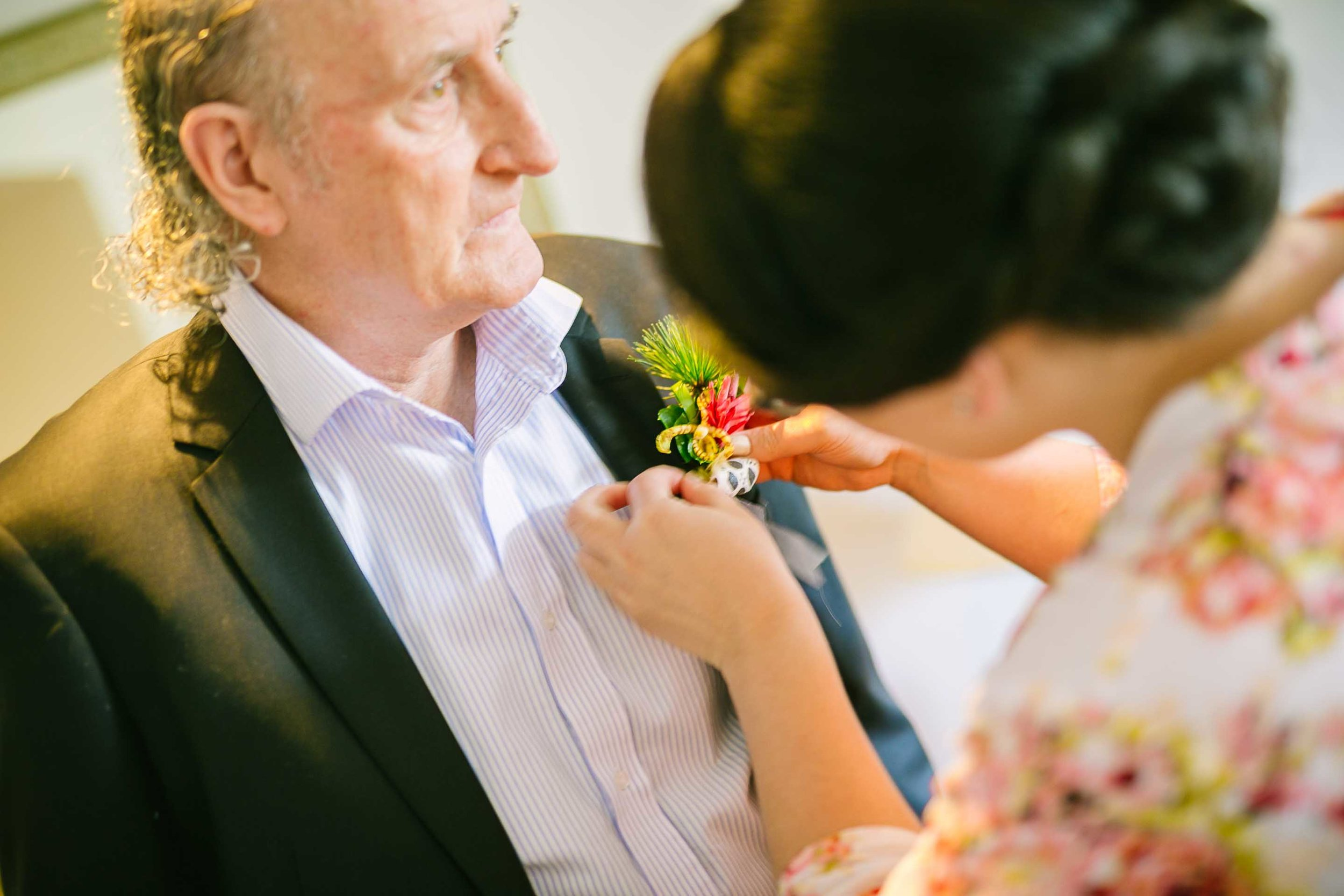 bridesmaid helping father of the bride with his Boutonnière