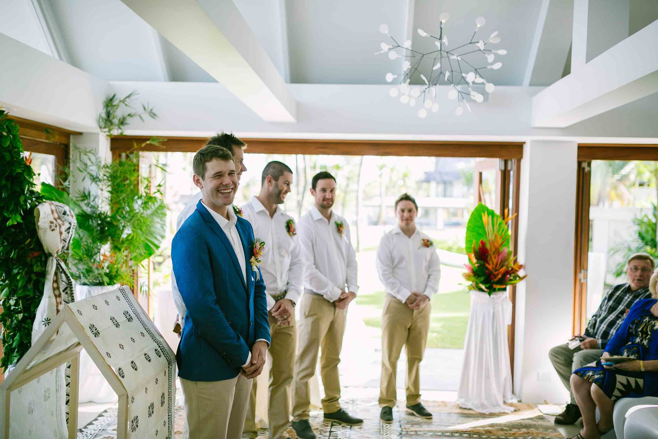 the groom and groomsman waiting at the end of the alter for his bride