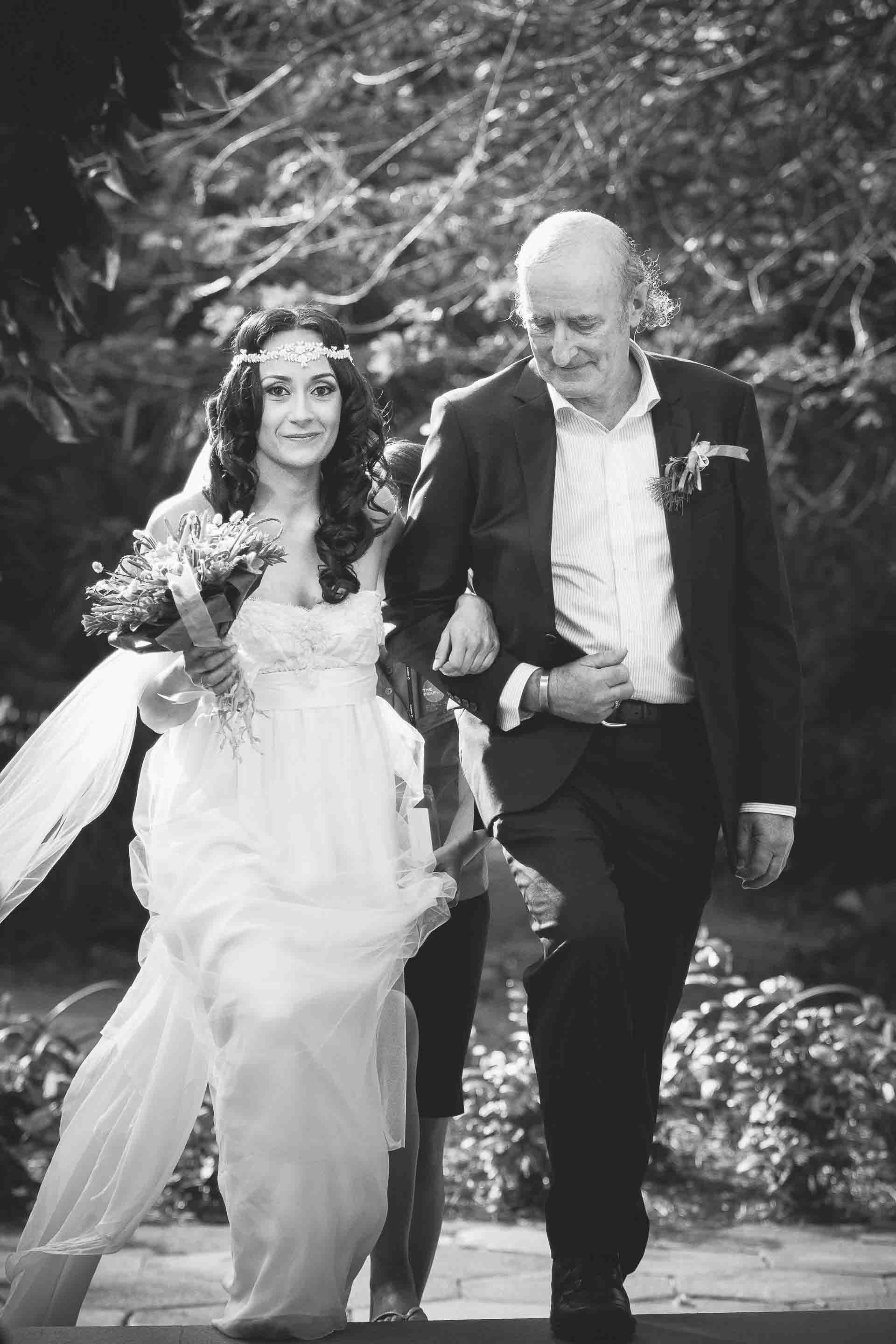 father of the bride escorting his daughter to the chapel