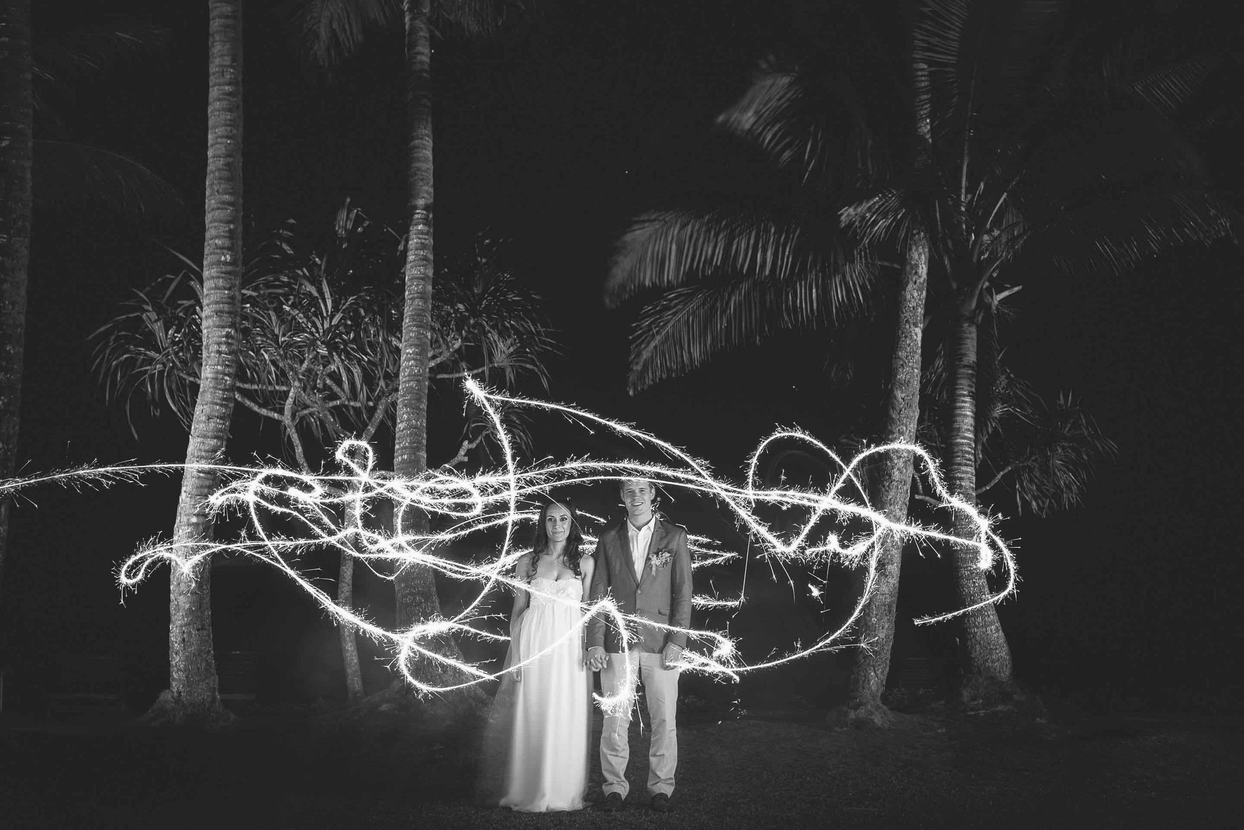 Newlyweds lit by sparklers