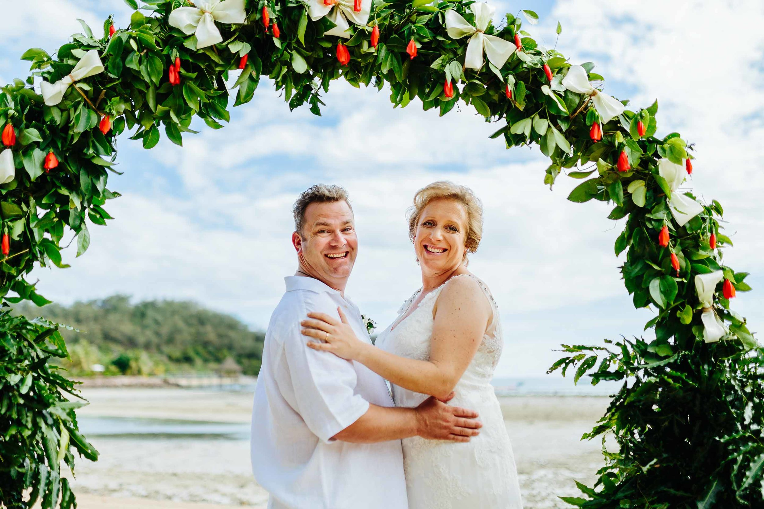 the couple under their wedding arch