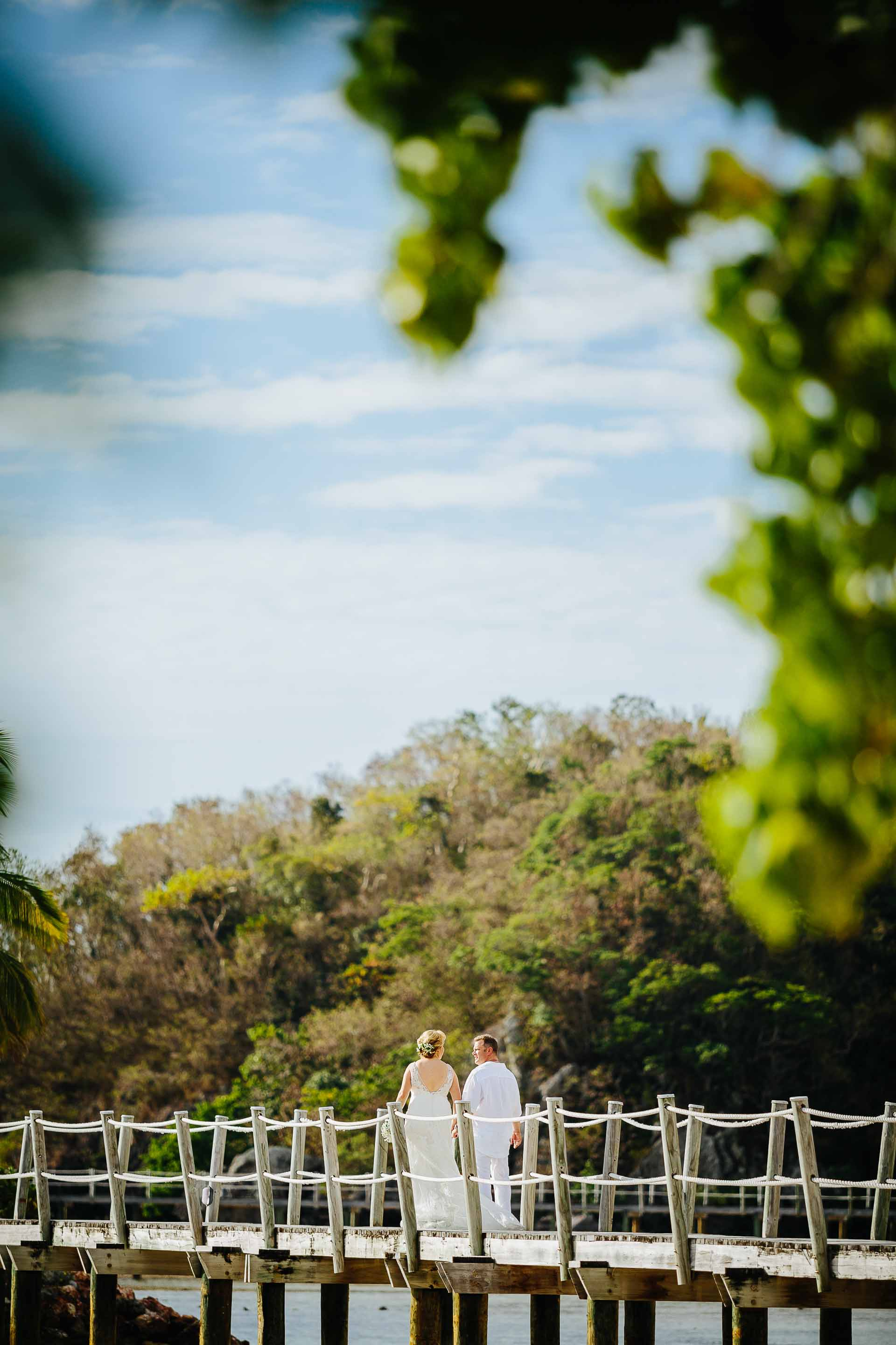the couple walking down the pier through the trees