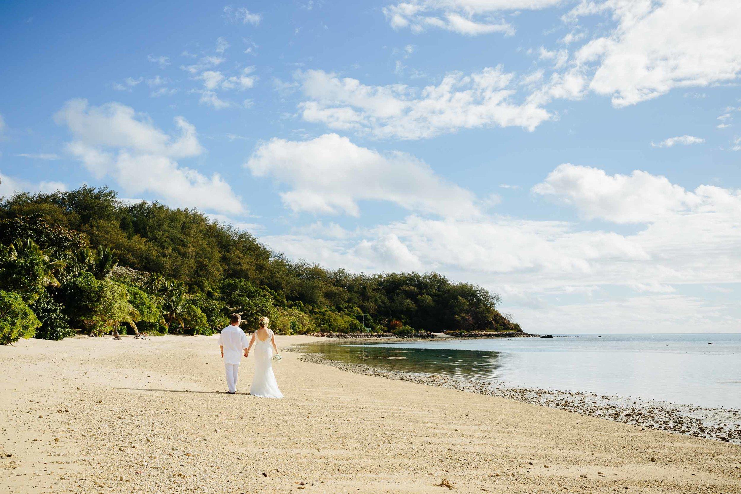 Newlweds walk down the beach in Fiji