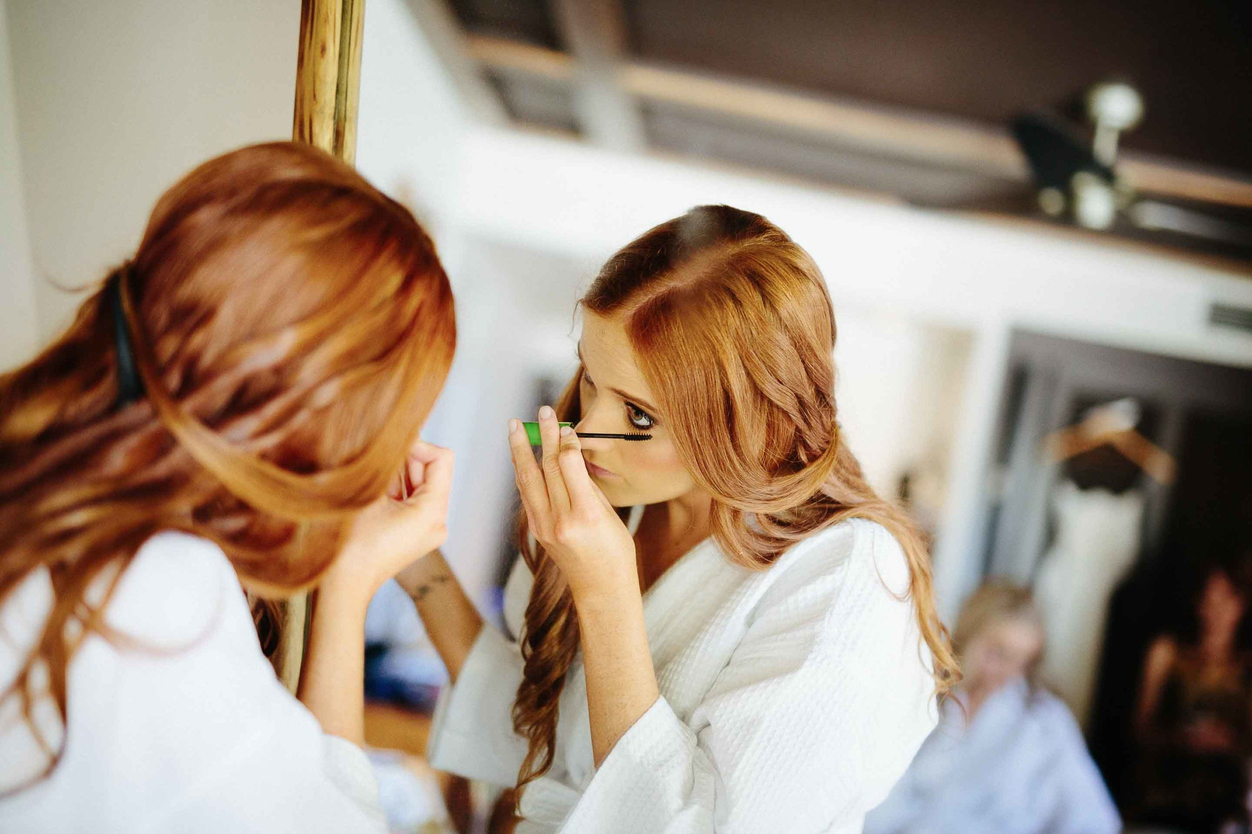 The bride applying her mascara in a large mirror