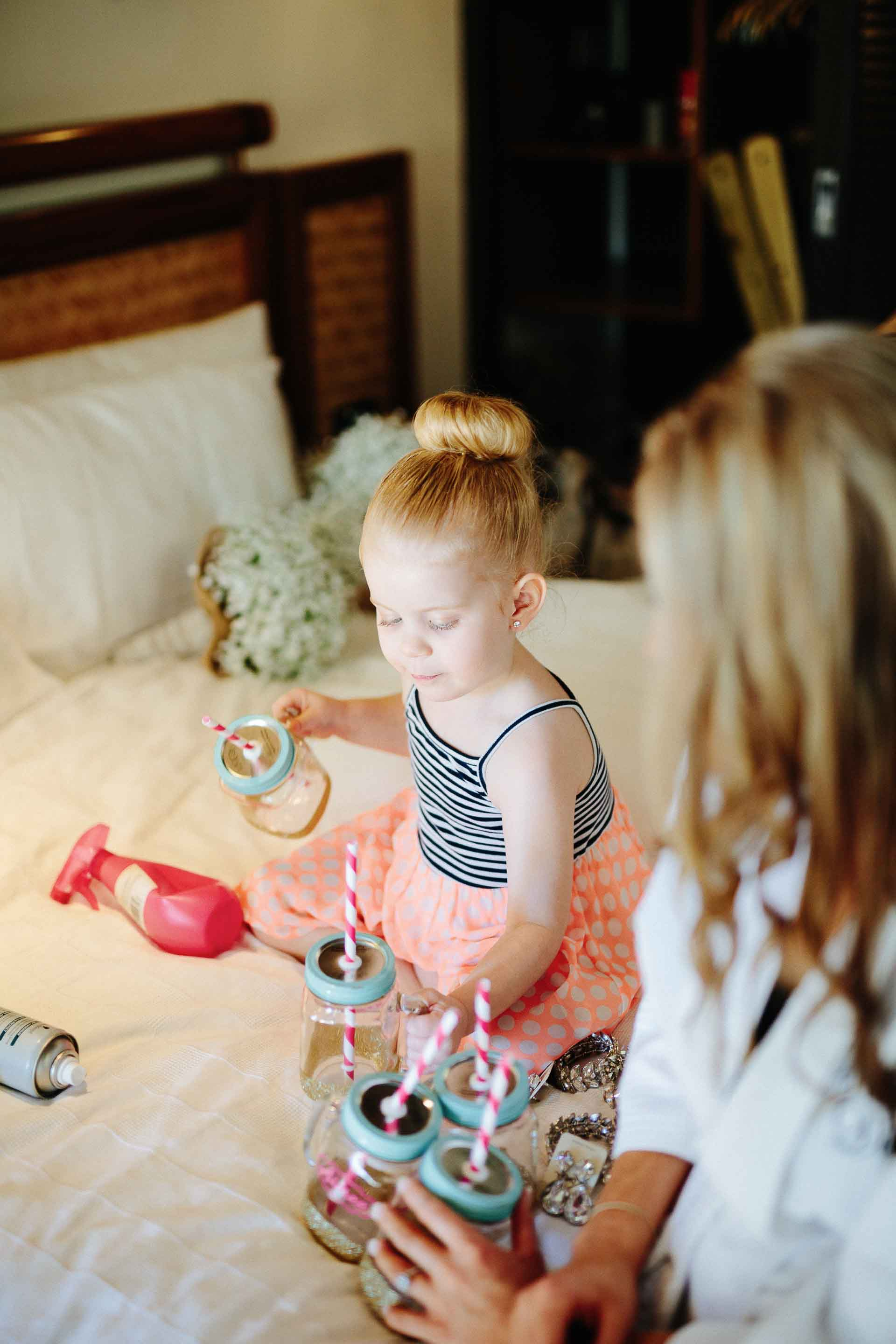 flower girl playing with the bridesmaids sippy cups