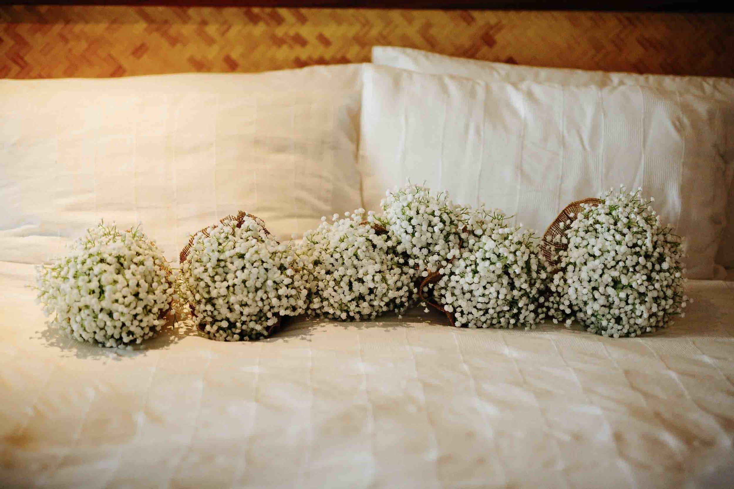 bridal bouquets lined up on the bed